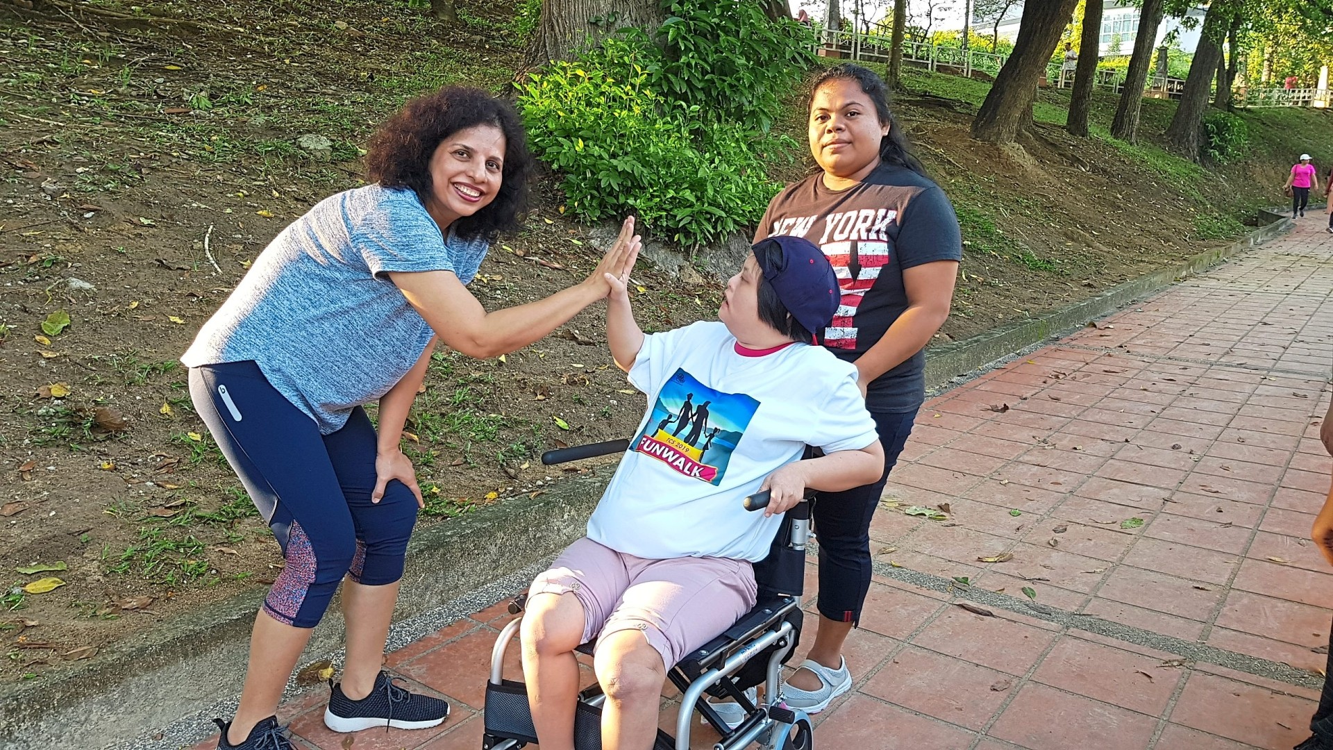 Dr Pushpa gives Wong Yong Xin, 29, a high five for taking part in the event. Wong is one of 25 differently-abled students who attend classes at Touch Community Seremban.
