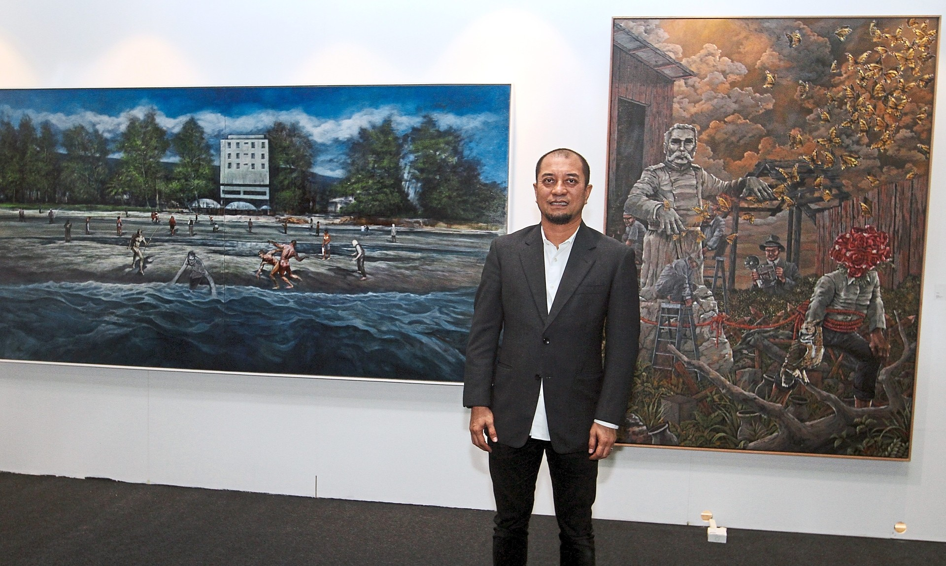 Nizam in front of two pieces by UiTM alumni during the Art Expo Malaysia 2019.