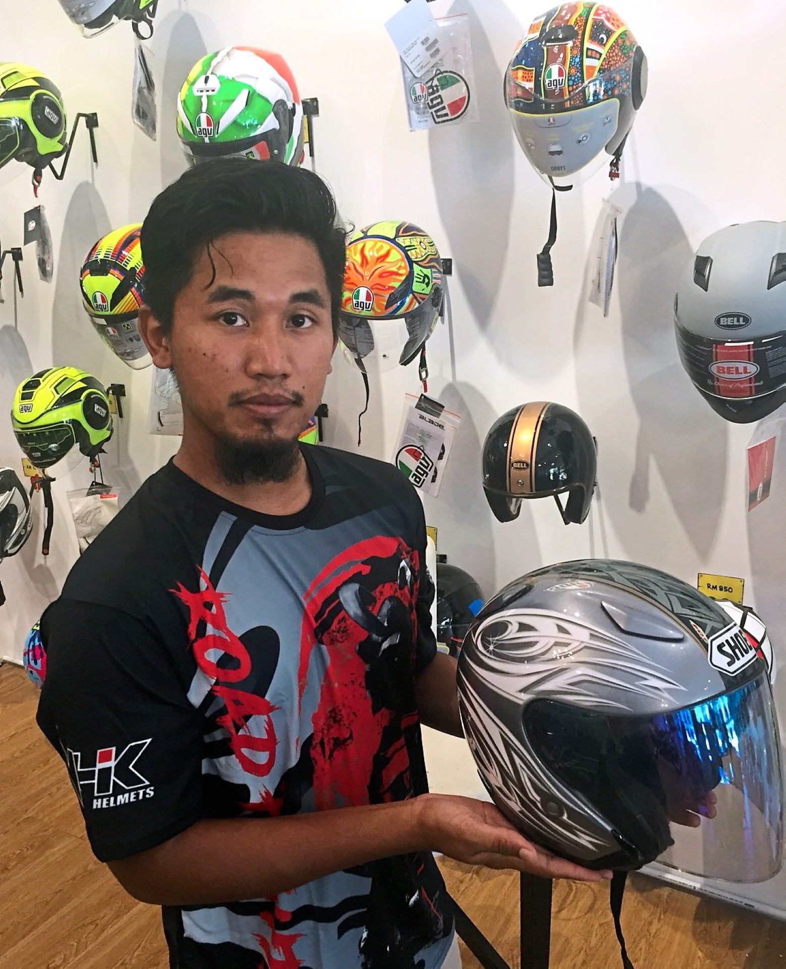 Safety first: Saifudin showing a Shoei motorcycle helmet priced at more than RM10,000 at his shop in Setia Eco Garden in Iskandar Puteri, Johor.