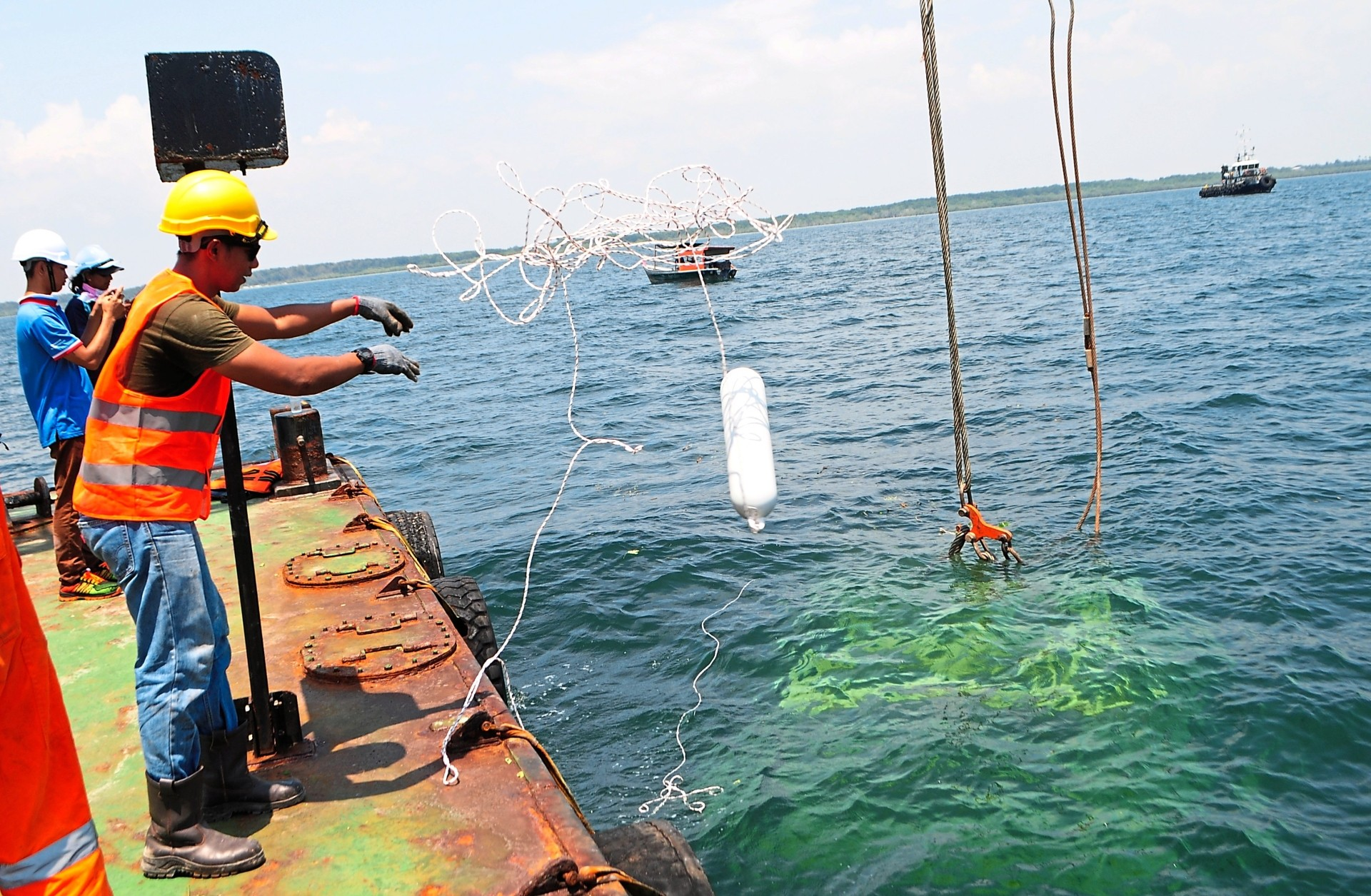 4) A worker throws a buoy which has been attached to the reef to mark its location.