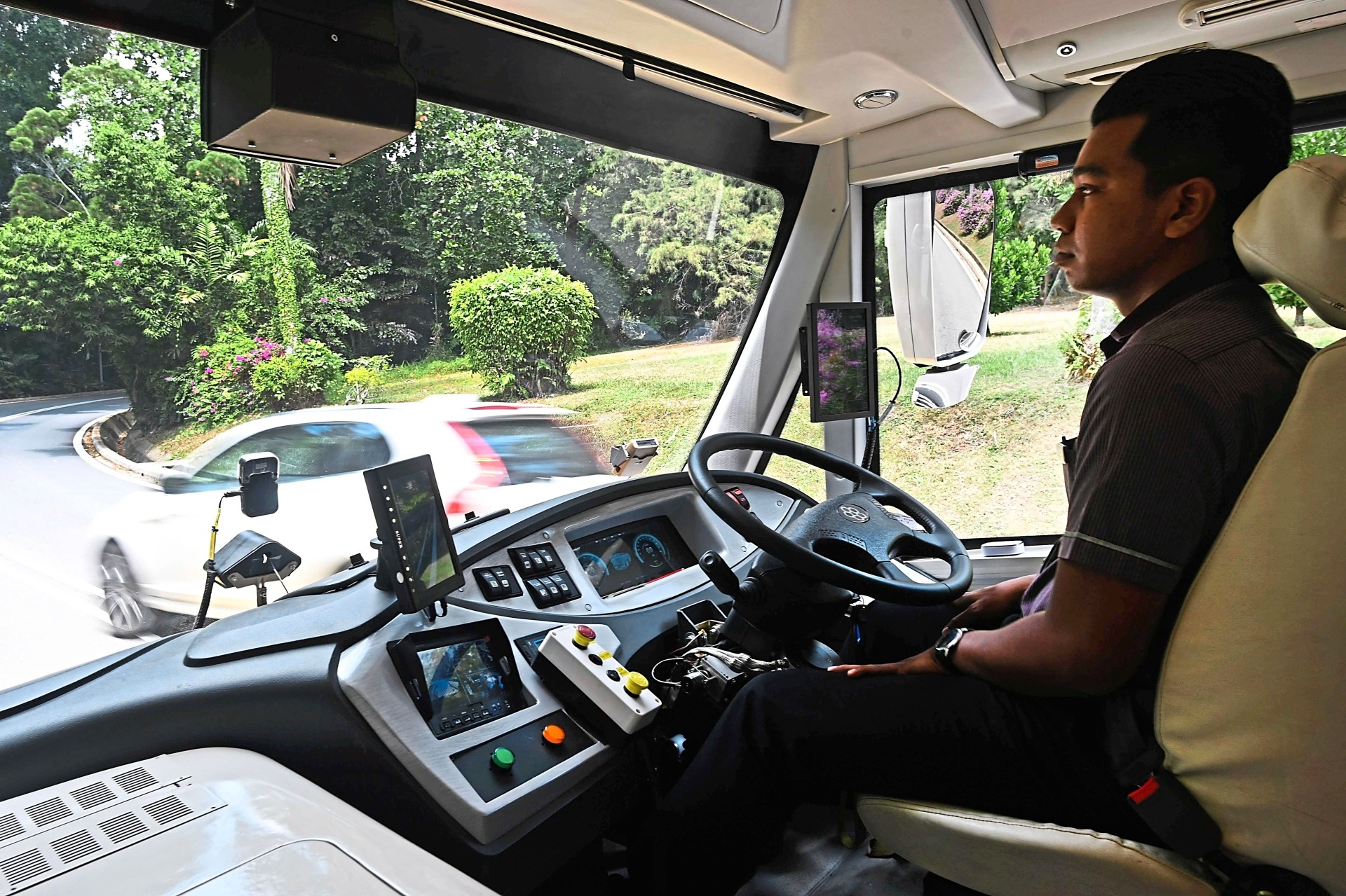 A safety driver sits in a moving on-demand autonomous shuttle bus at the official launch of a public trial in Sentosa island resort, Singapore. — AFP