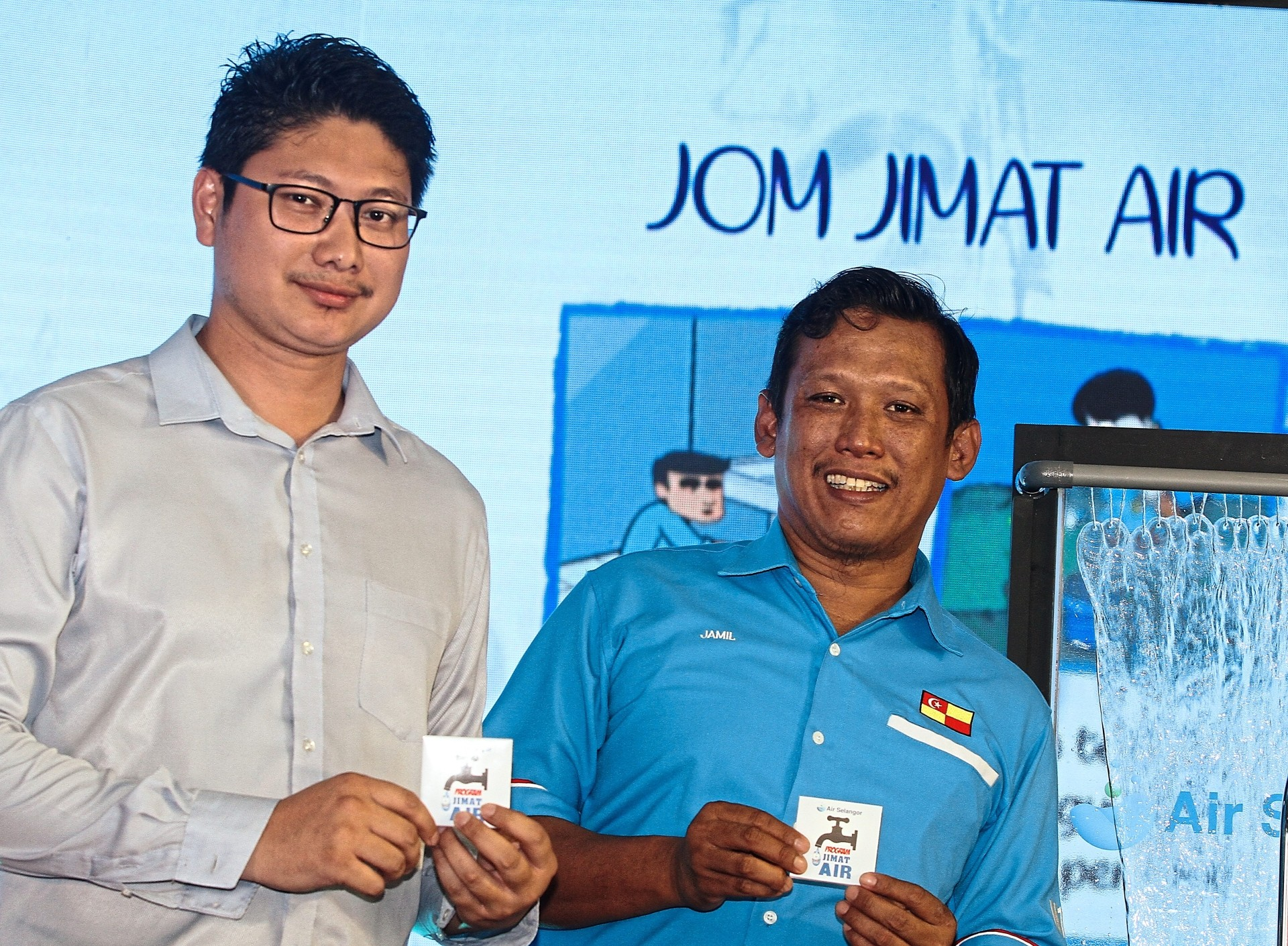 Taman Selayang committee member Mohd Azri Abd Rahman (left) and Kampung Sungai Kertas village chief Jamil Azaman Razak with their water thimbles. Both are dedicated to playing their part in water conservation by educating the community on saving water.