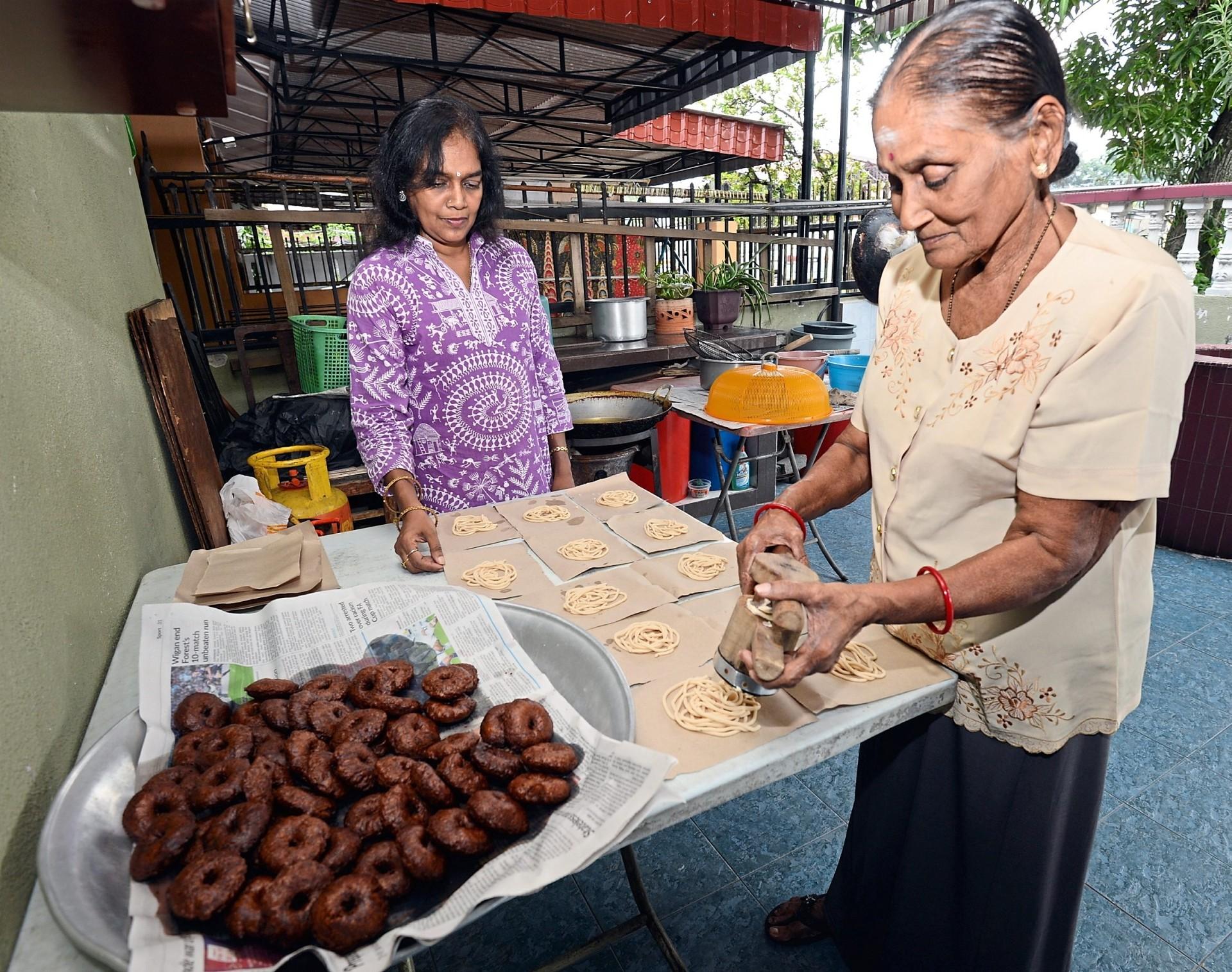 Vijialetchmi (right) and Shela Devi preparing murukku and athirasam at their home in Taman Bertek, Klang.