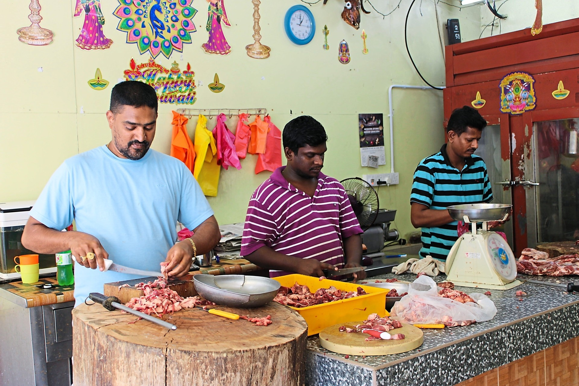 Purusuthaman (left) chopping mutton for customers alongside workers, Muninathan Manthaiyan, 29 (second from left) and Sevugamoorthi at Papa Mutton Shop in Brickfields.