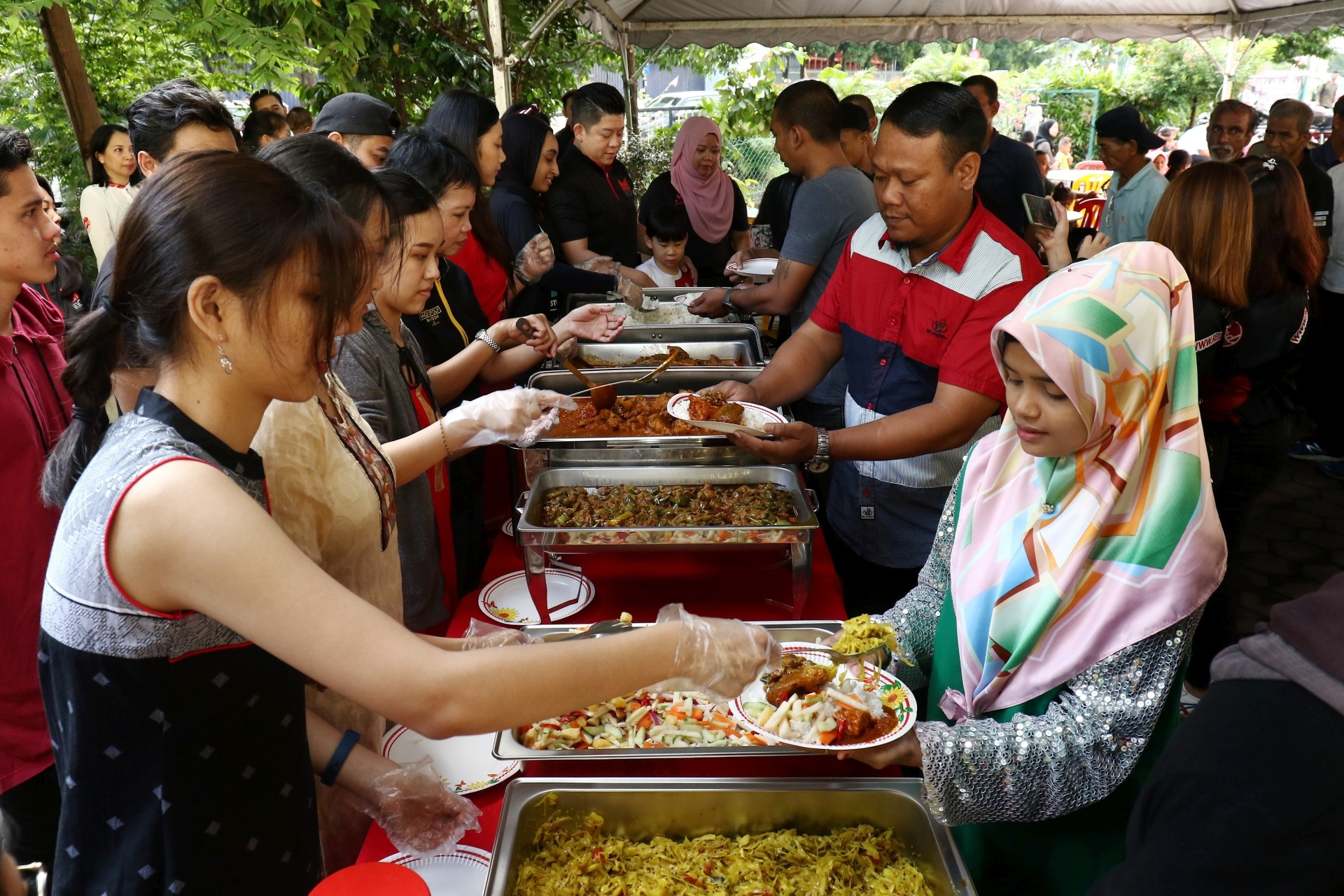 The volunteers (left) serving food to the residents at the transit home. — Photos: FAIHAN GHANI and MOHD SAHAR MISNI/The Star