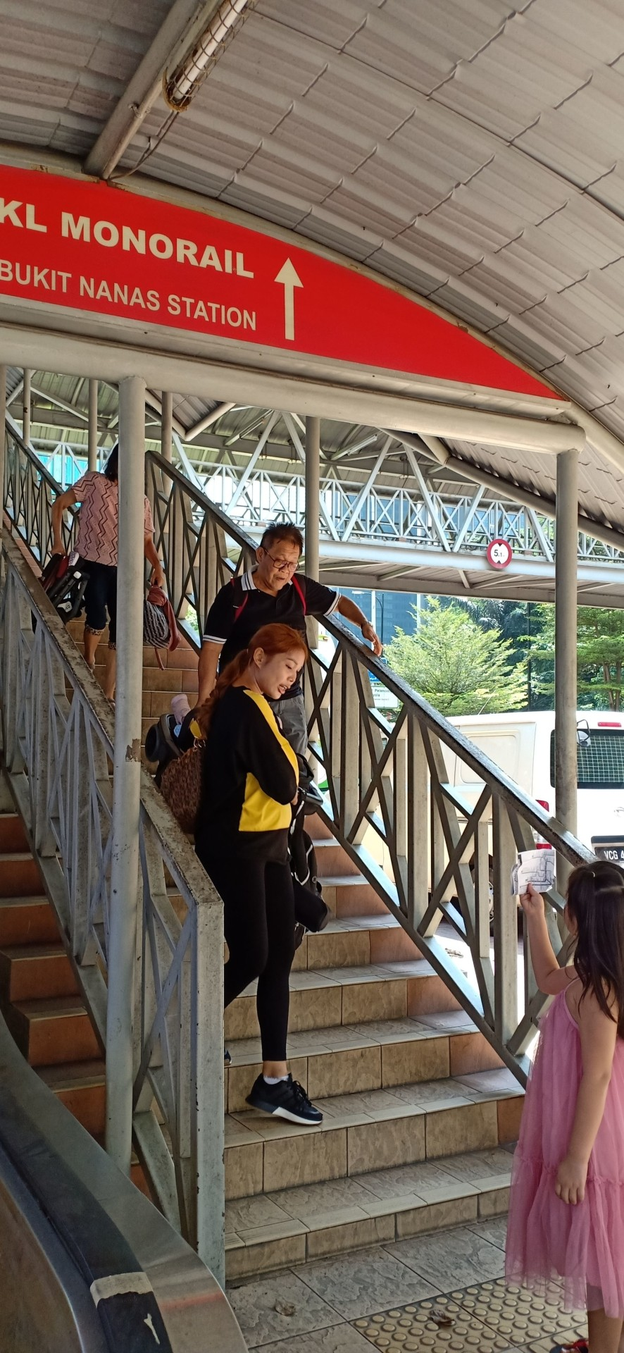 Some commuters lugging their luggage down the staircase of the pedestrian bridge because the escalators are out of order.
