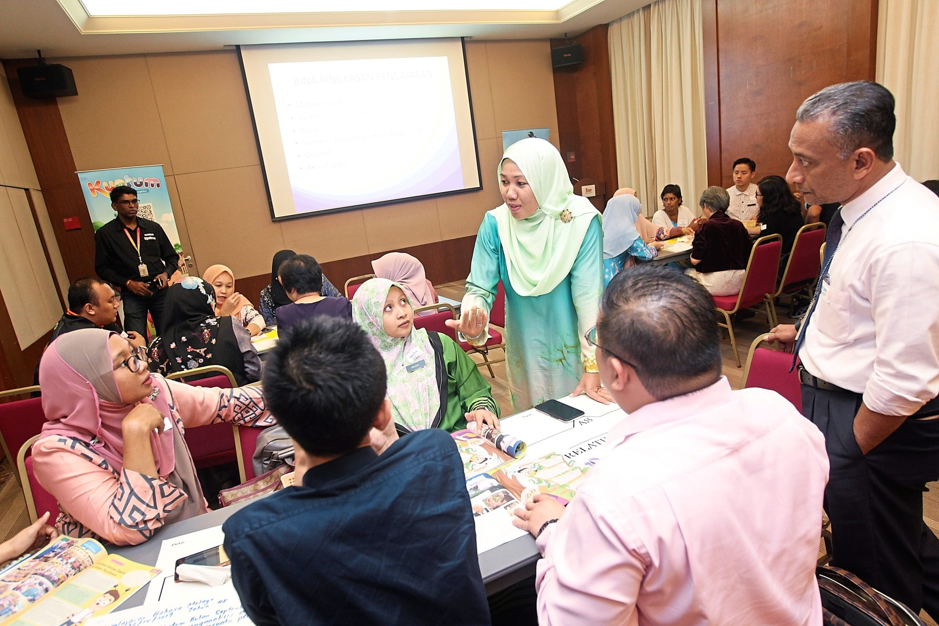 Norafizah (in green baju kurung) facilitating a workshop for primary library and media teachers from Kuala Lumpur and Selangor while Mohd Zaki (right) looks on.