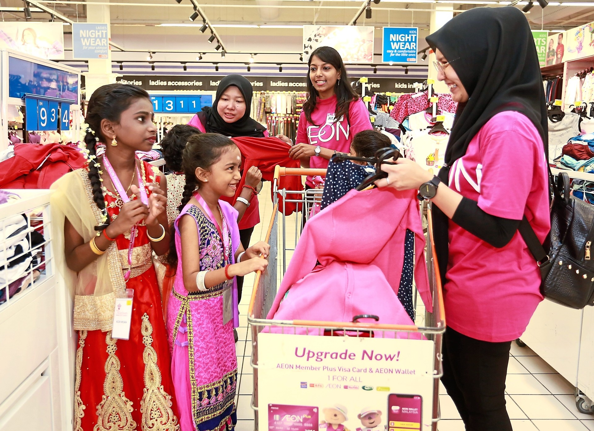 Aeon group volunteers assisting children as they shop for Deepavali clothes.