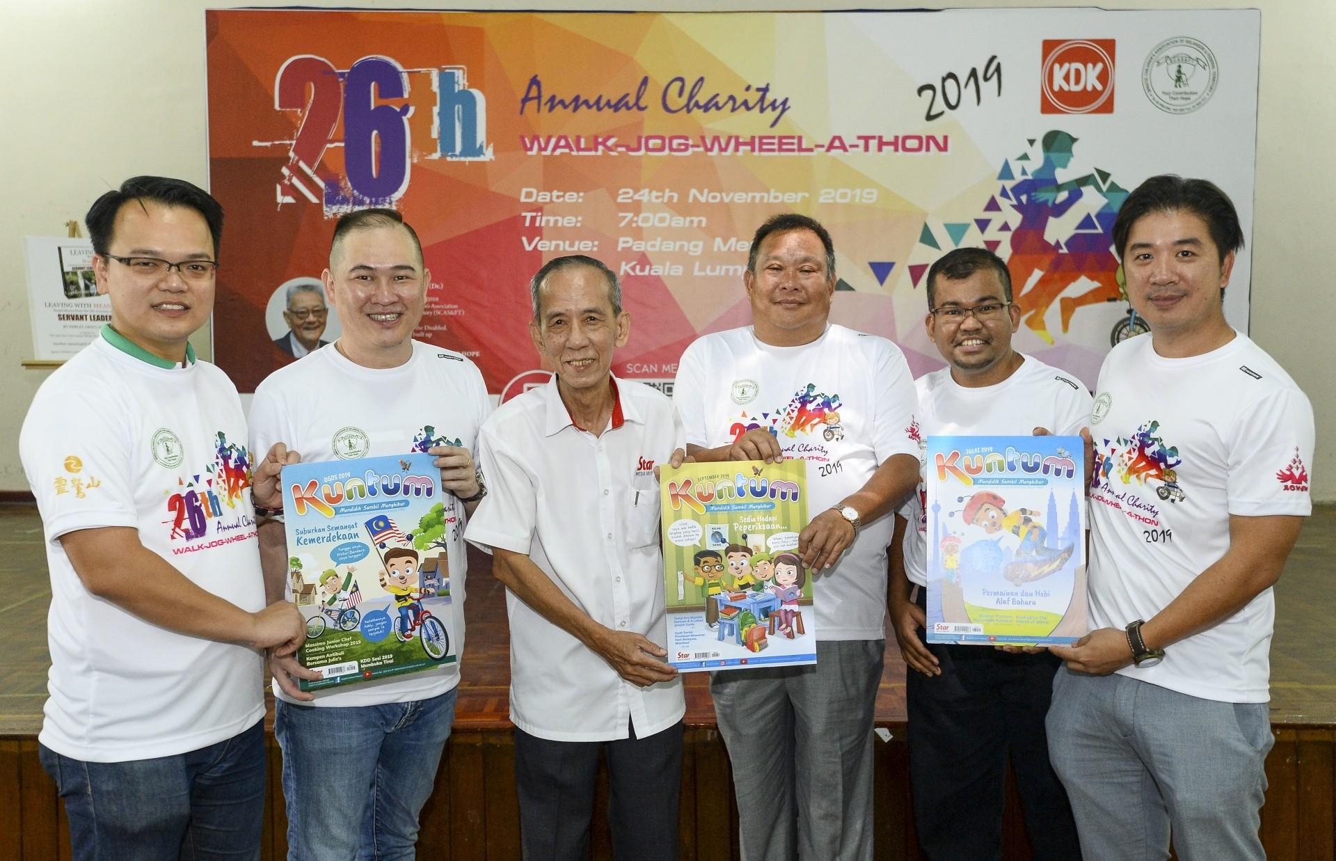 Loo (third from left) handing over Kuntum magazines to the Walk-Jog-Wheel-a-Thon organising committee members.