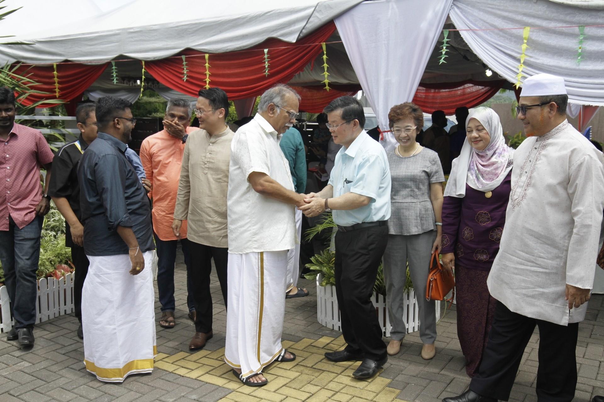 Ramasamy (white dothi) greeting Chow at his Deepavali open house at Bandar Tasek Mutiara in Simpang Empat, Penang. —Photos: CHAN BOON KAI/The Star