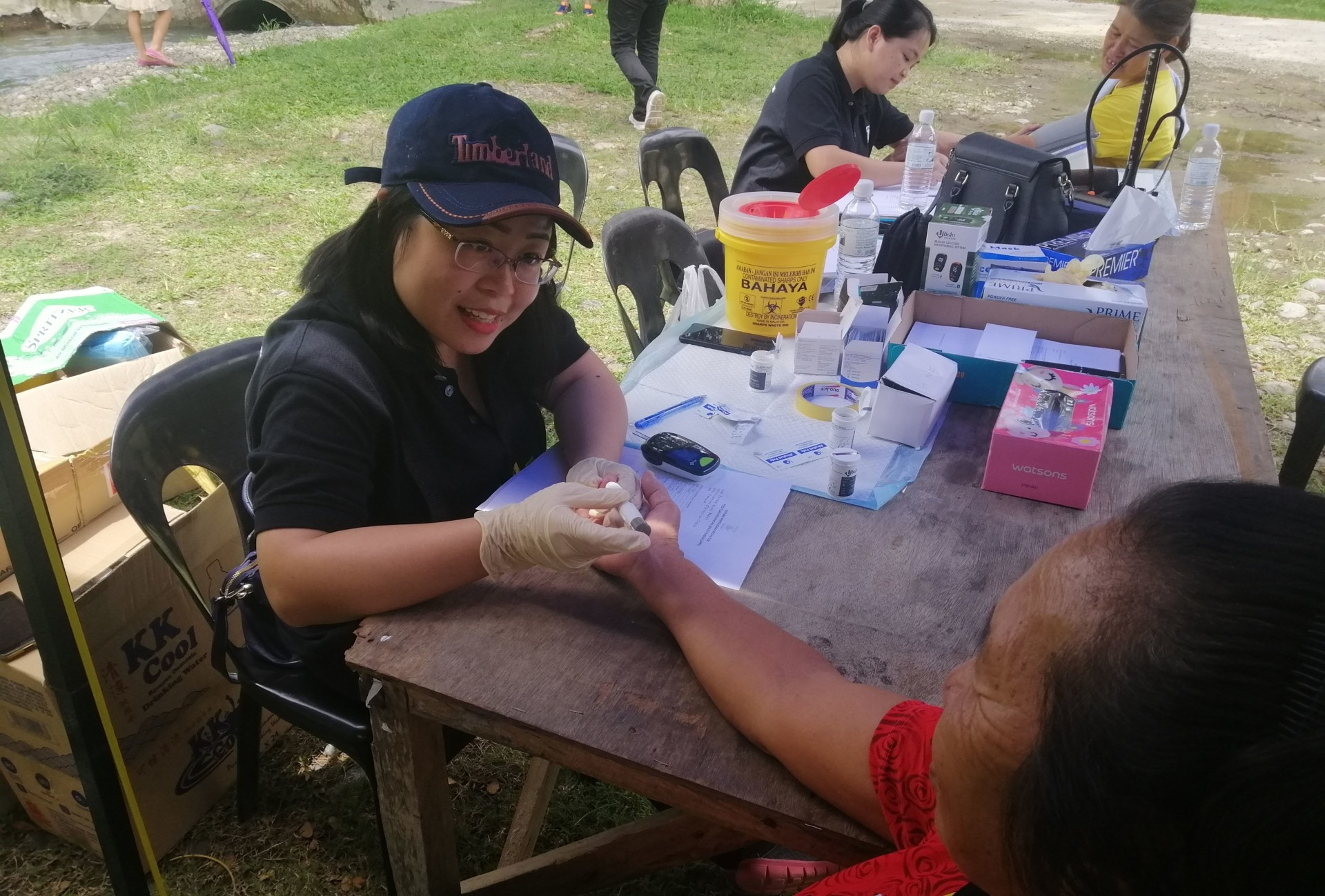 A nurse pricks a patient's finger to test for blood type. All the tests and medications at the camp were free for the patients.