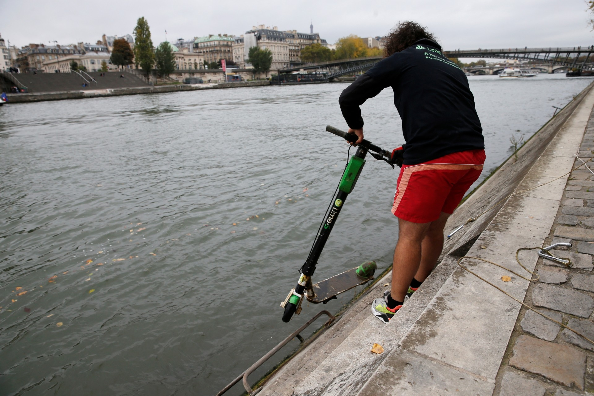 A Lime employee fishing an abandoned electric scooter Lime-S out of the River Seine in Paris, France.