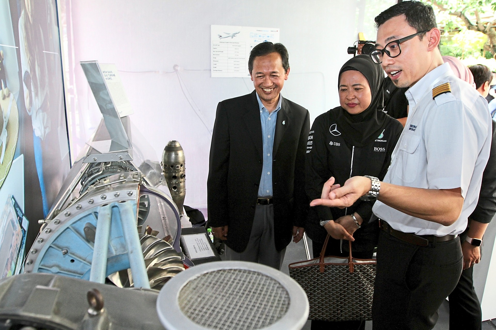 Licensed aircraft engineer Mohd Faridz Mohd Shuraimi (right) describing the  workings of a replica of a gas turbine engine to Zahariah (centre) at the Malaysia Airlines booth.