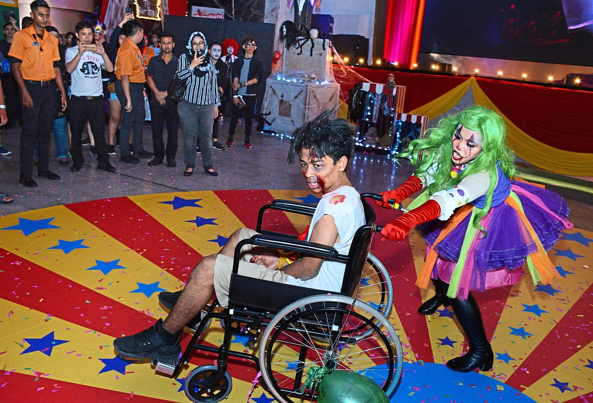 A scary clown terrorising a victim during the performance themed 'A Nightmare on Killer Clown Street'.