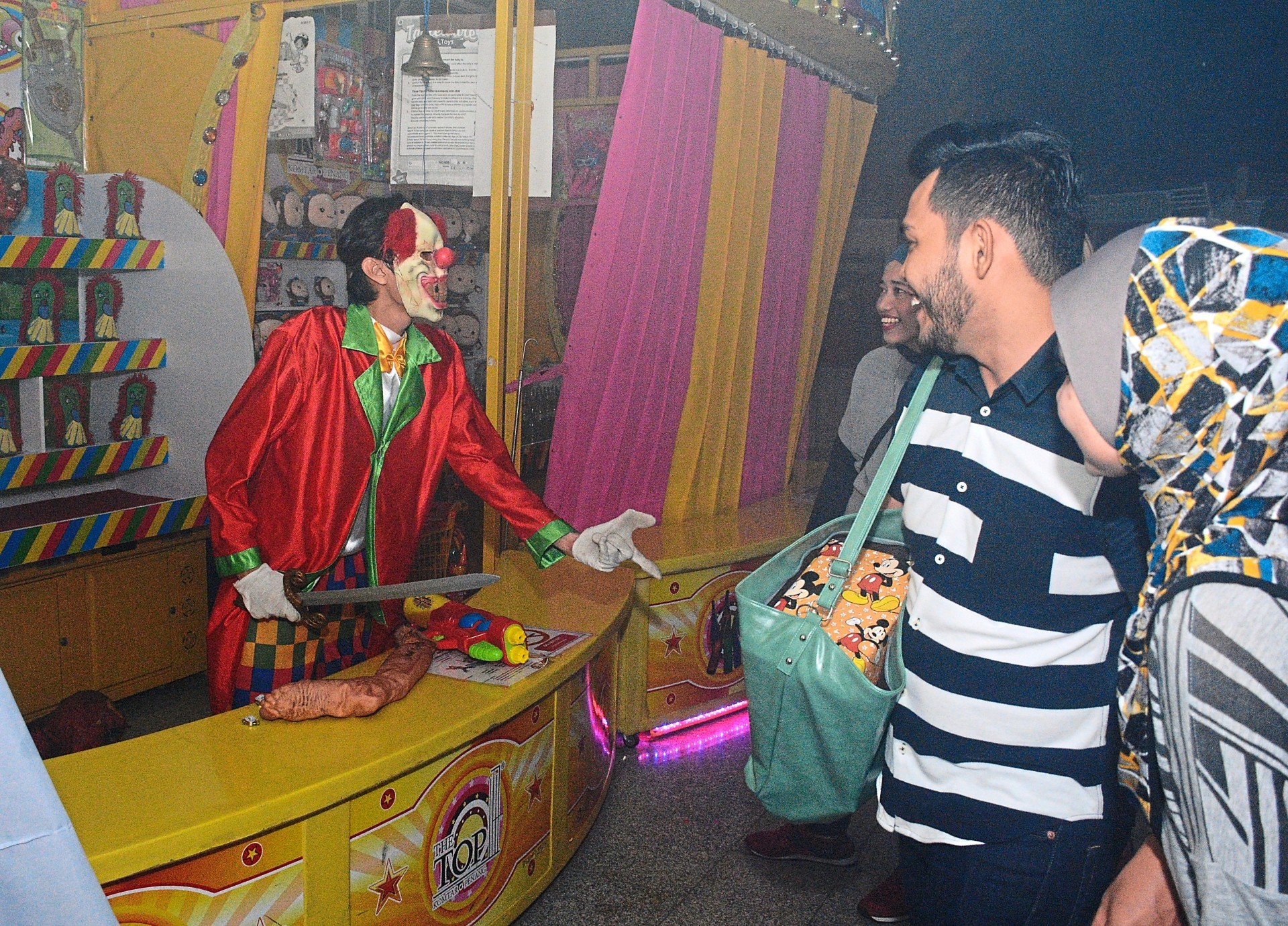 Visitors checking out the killer clown booths located inside the 'haunted house'.