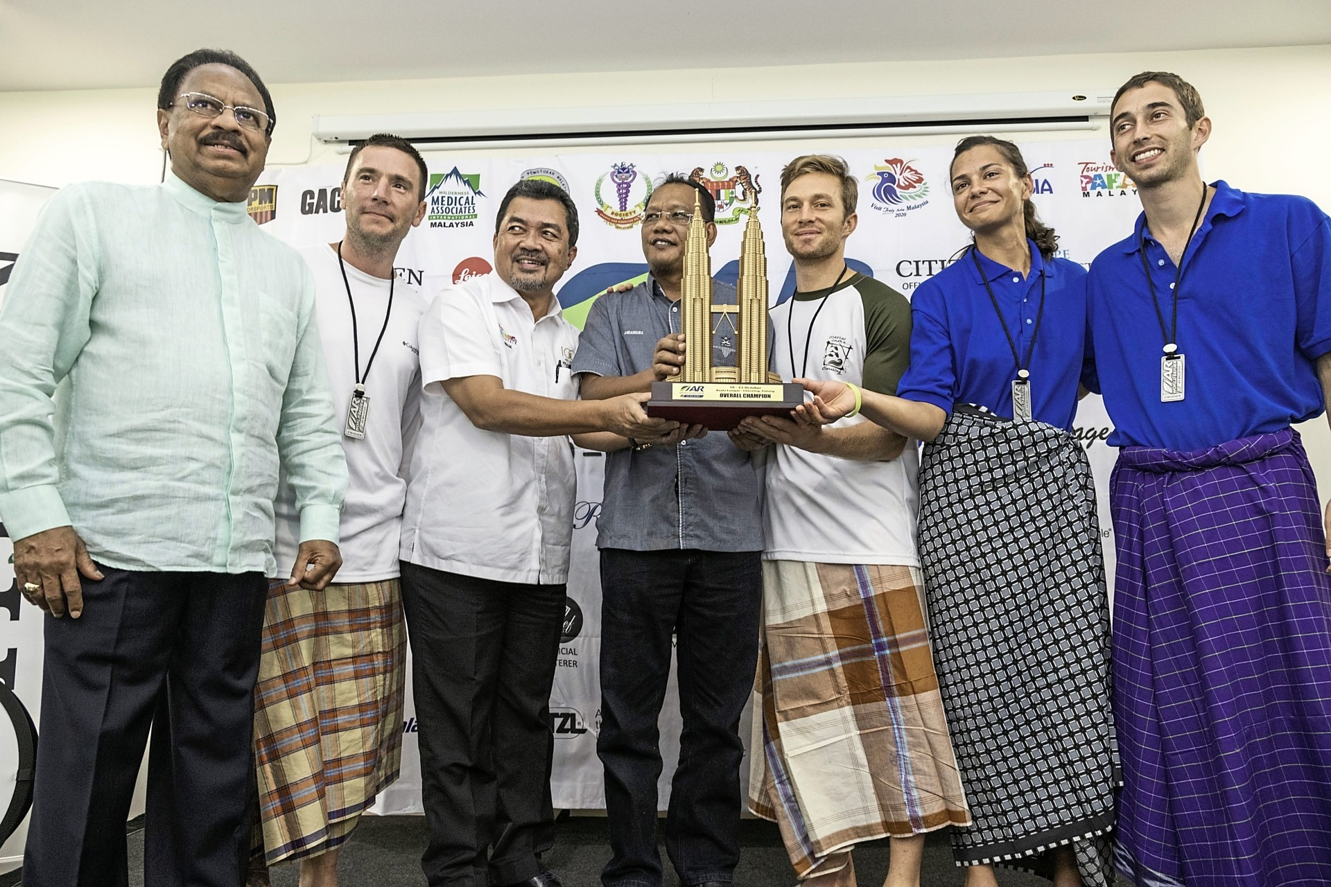 Dr Mohamed Mydin (left), Tourism Pahang general manager Datuk Ishak Mokhtar (third from left) and Beserah assemblyman Andansura Rabu (centre) presenting the winning trophy to members of Team Altitude of the United States, who were clad in sarongs.