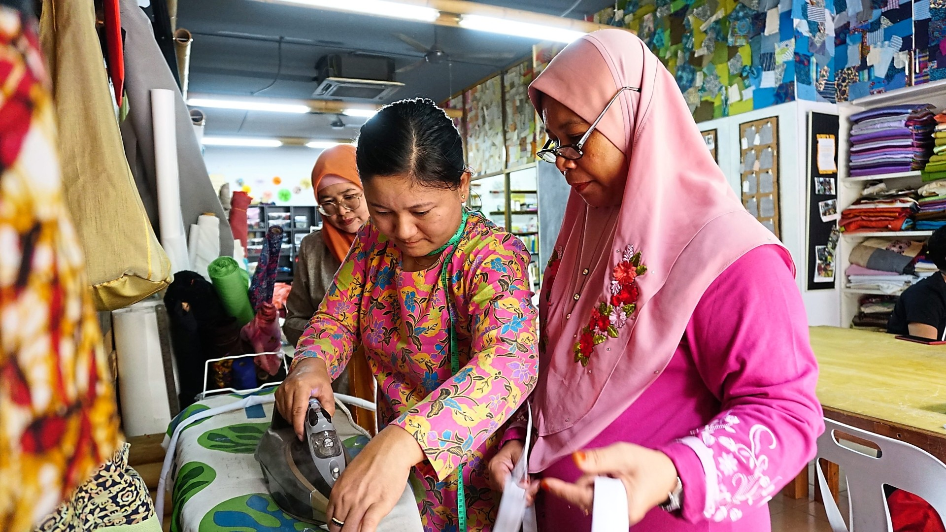 Sew x Dignity staff guiding Kain Movement's talents during one of the sewing workshops.