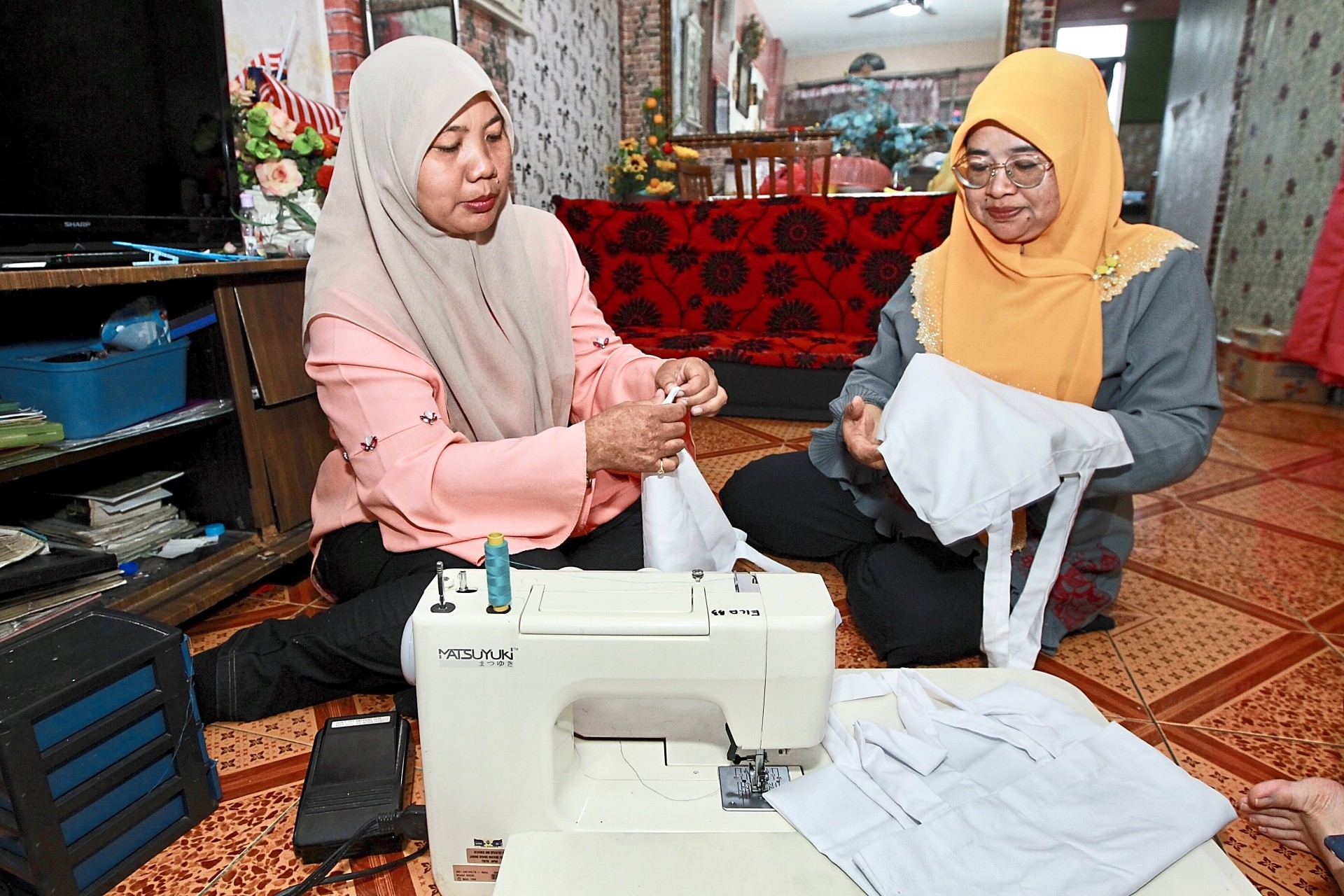 Zaitun (left) and Ila discussing their work at the latter's unit in Desa Mentari, Petaling Jaya. — Photos: NORAFIFI EHSAN and SHAARI CHEMAT/The Star and courtesy of Kain Movement