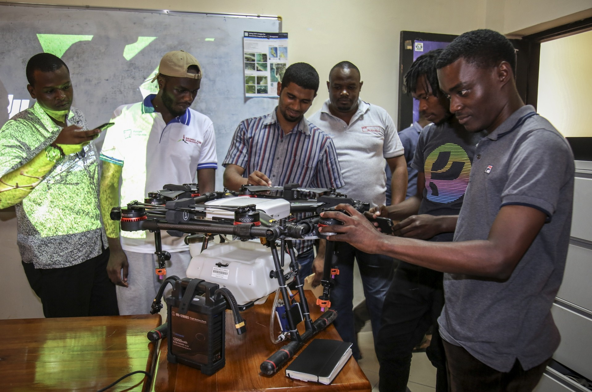 Trainee drone pilots from the State University of Zanzibar examine a drone to be used to spray the breeding grounds of malaria-carrying mosquitoes, at Cheju paddy farms in the southern Cheju region of the island of Zanzibar.