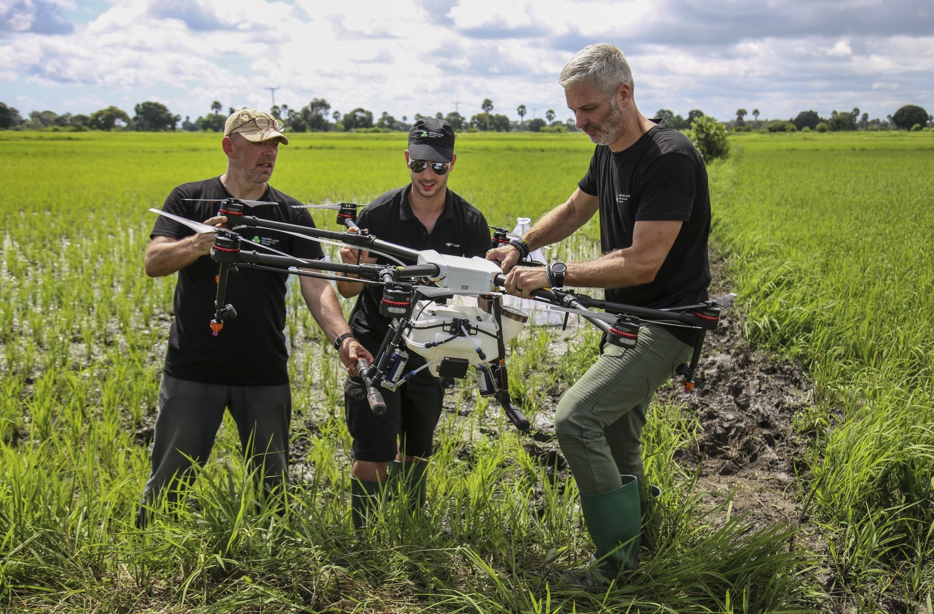 Knols (left), Rodriguez (centre) and Guido Welter, a consultant from the Anti-Malaria Drones programme, preparing a drone to spray the breeding grounds of malaria-carrying mosquitoes, at Cheju paddy farms.