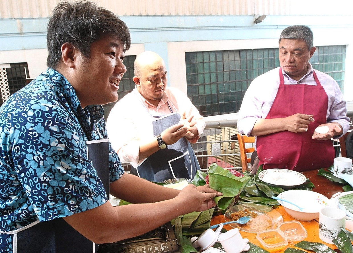 Sean Tan (left), a tour guide who leads some of the heritage walks in Kuala Lumpur, shows guests how to make some traditional delicacies during the food experience.