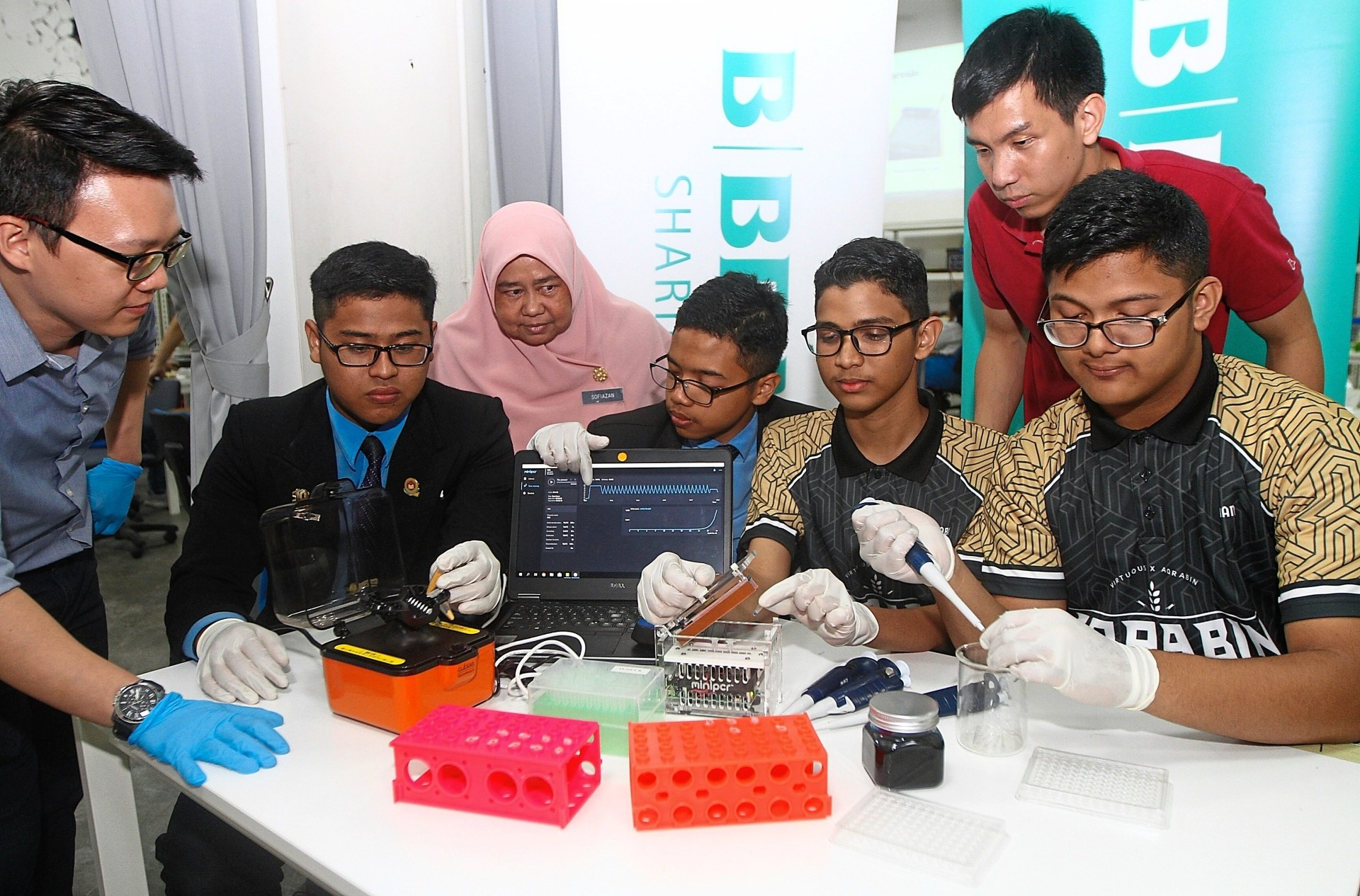 Penang Science Cluster staff Winson Koe (left, SMK Agama Al-Irshad biology teacher Sofiazan Mohd Yusof (3rd from left) and LIR Biotech Sdn Bhd business development executive Josiah Liew (2nd right) assisting students in using the DNA learning kits.
