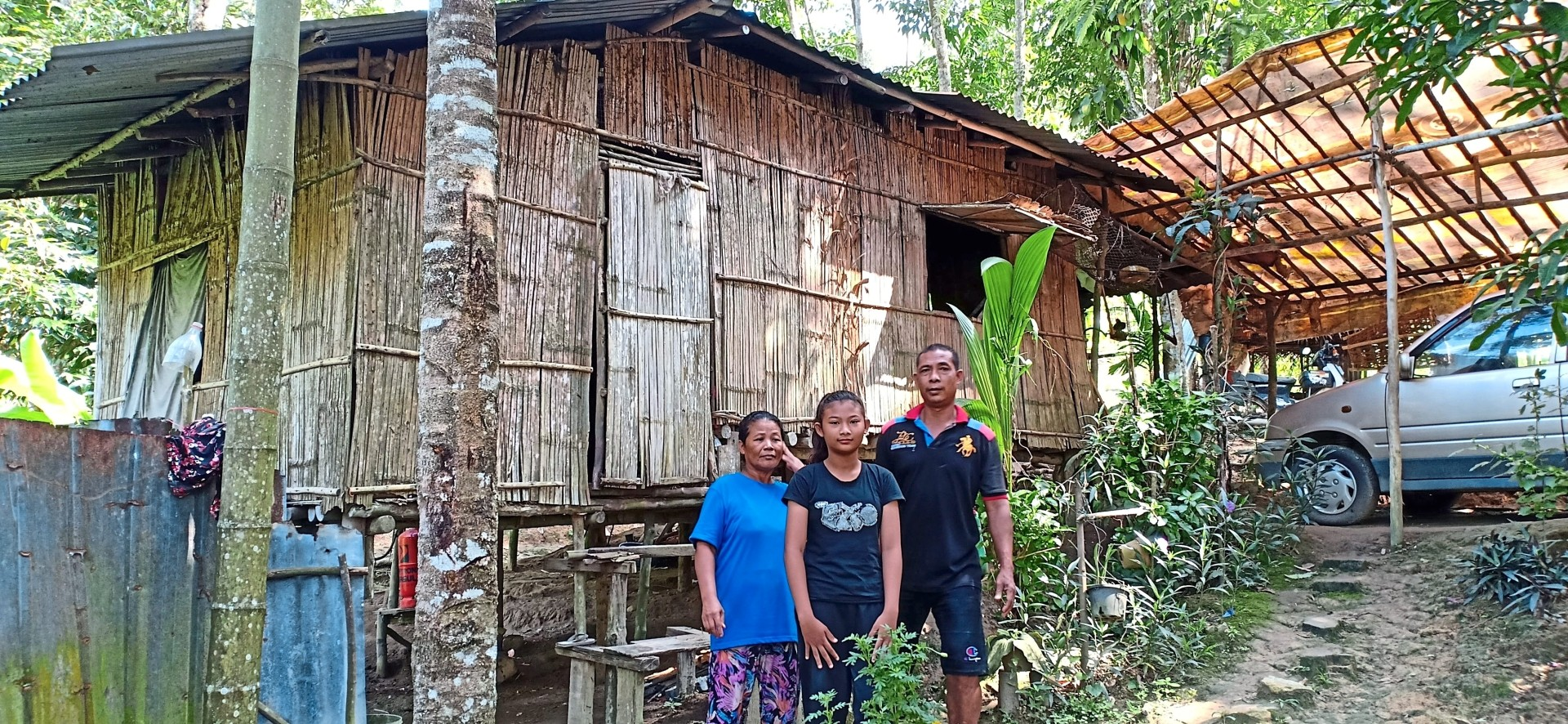 Tepi Teresa Takam, Sari Atan and their youngest daughter standing in front of their old home, which was built from bamboo.