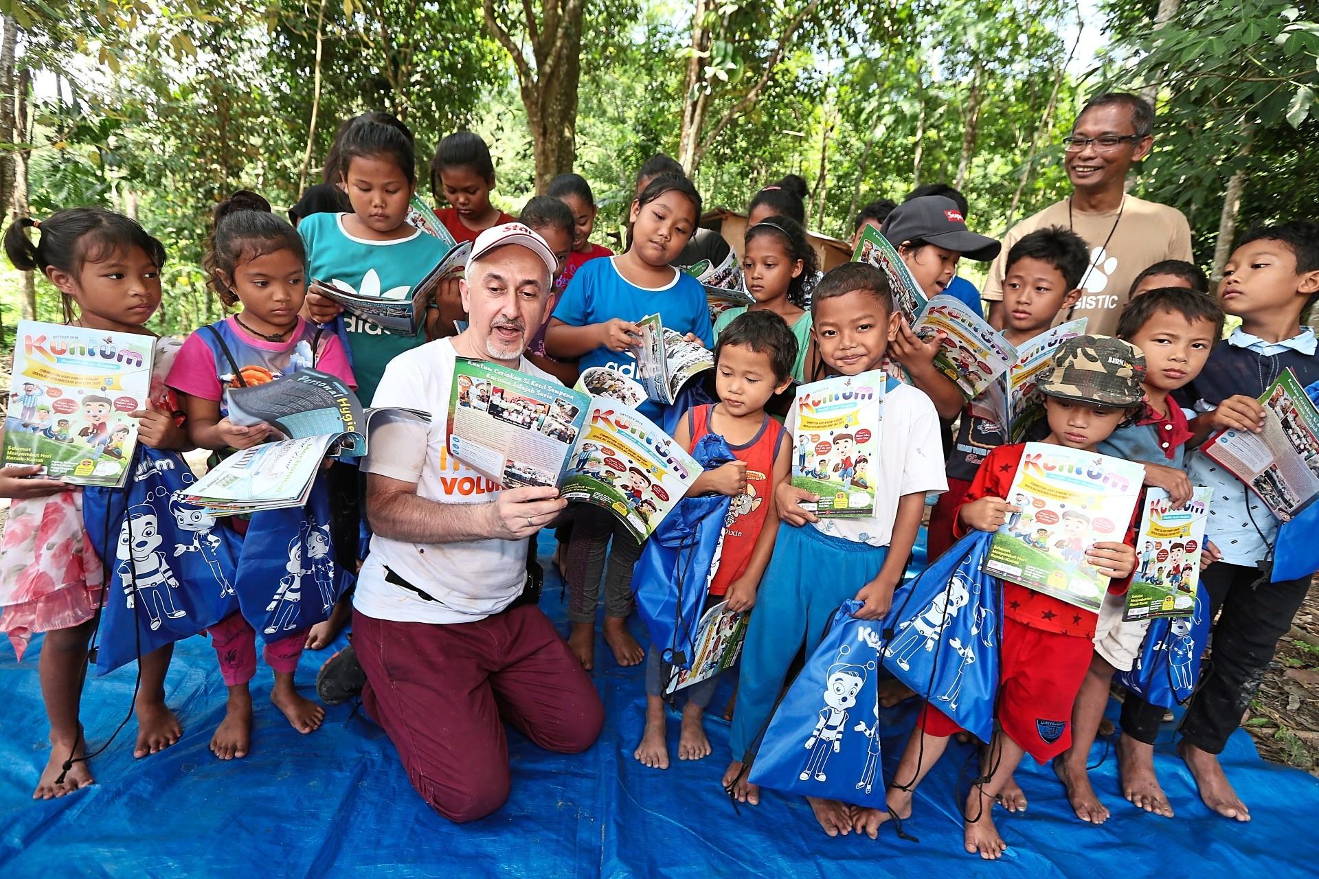 Vogiatzakis showing the Kuntum magazine to the Orang Asli children.