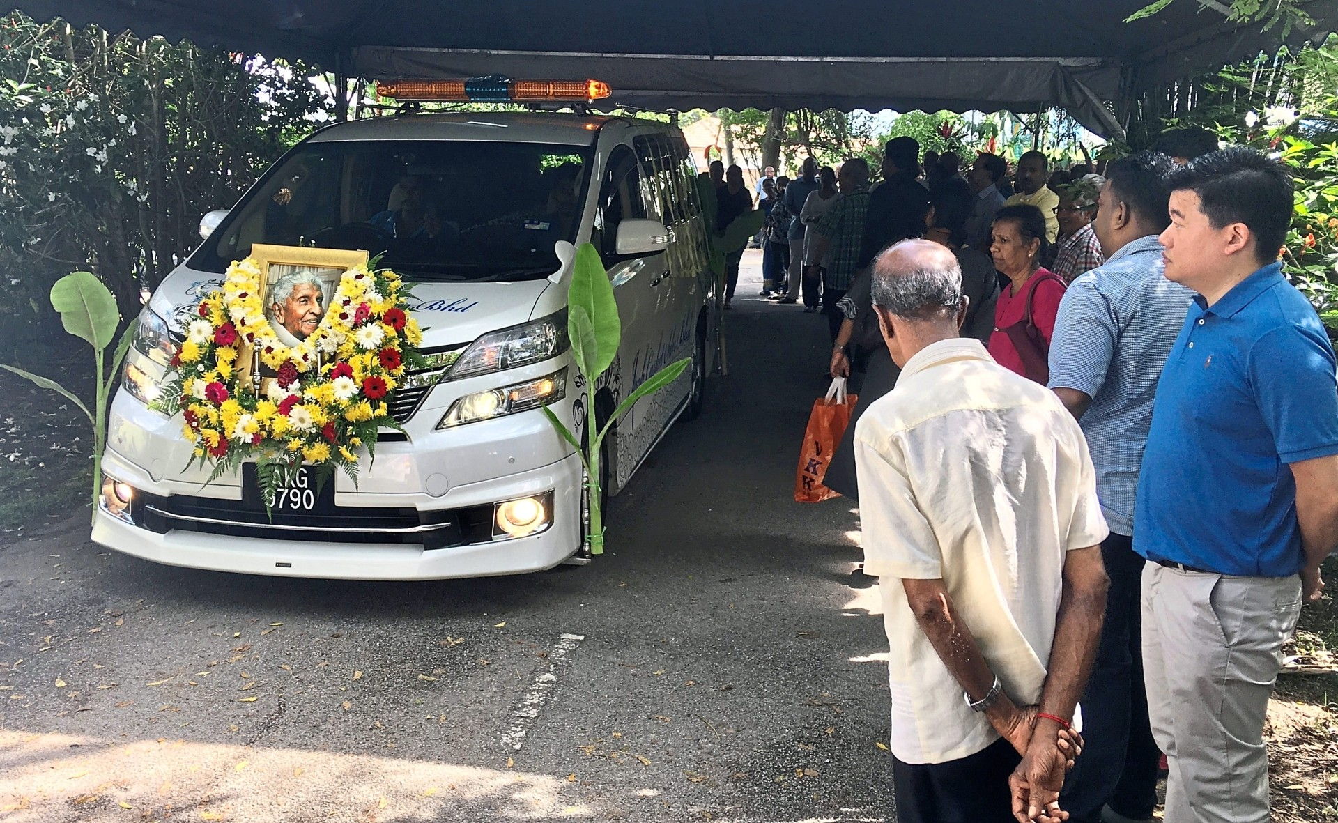 Family and friends standing along Persiaran Anderson, Ipoh, to give Selvamany a final send-off on Saturday.