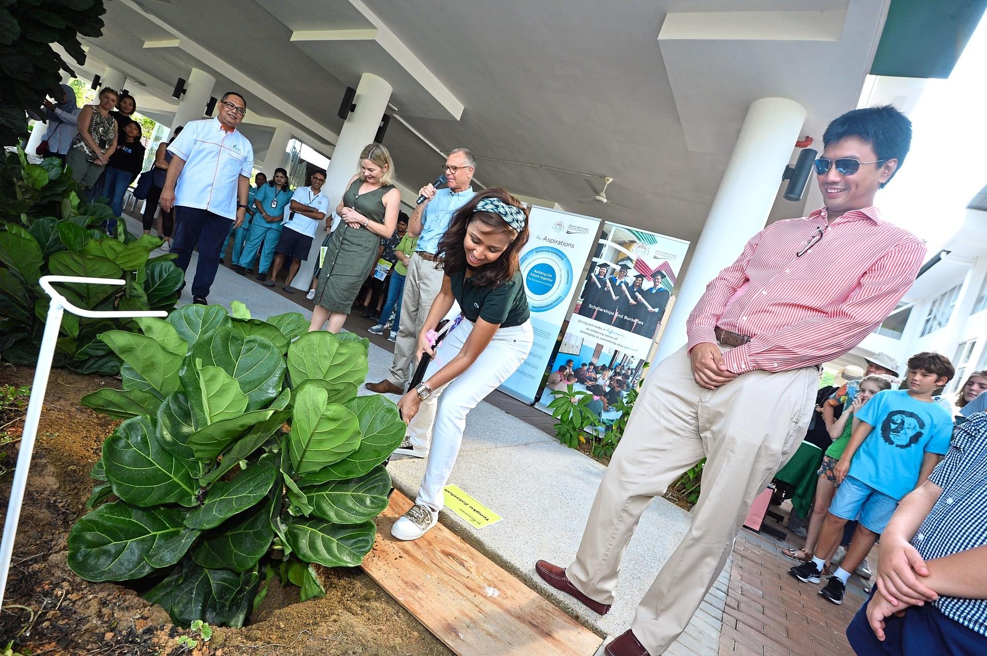 Tengku Zatashah planting a merbau tree at the school's foyer while school alumni Tunku Zain Al-'Abidin (right) looks on.