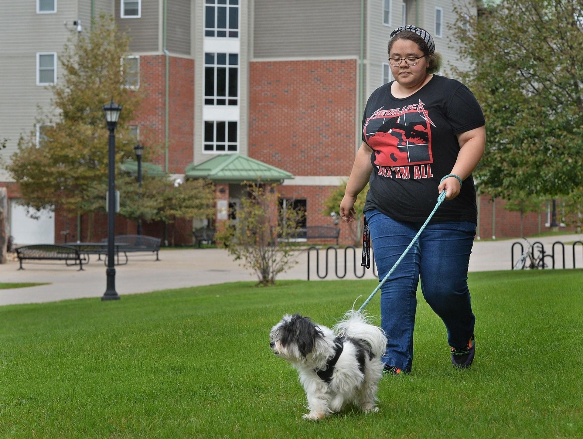 Elaina Krafick walks her dog, Loki, near the Lawrence Towers dormitory at Edinboro University of Pennsylvania, the United States. Krafick, 21, is one of six pet owners living on the new pet-friendly floor at the dorm.
