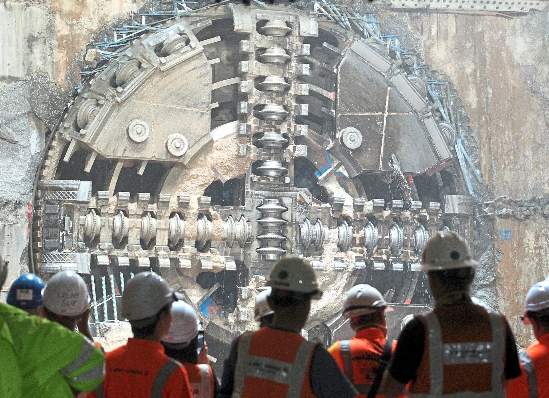 Excited over boring machine: Workers cheering the breakthrough of the tunnel boring machine at the Ampang Park MRT station.