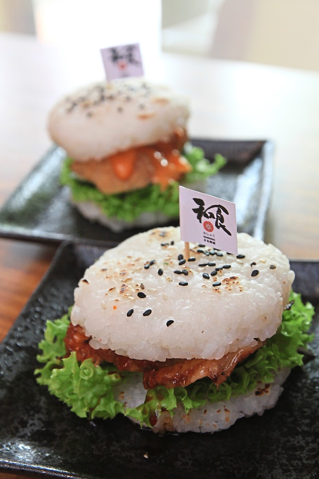 Unagi Sushi Burger (front) and Hot and Spicy Tori Karaage Sushi Burger use sushi rice patties as the burger bun.