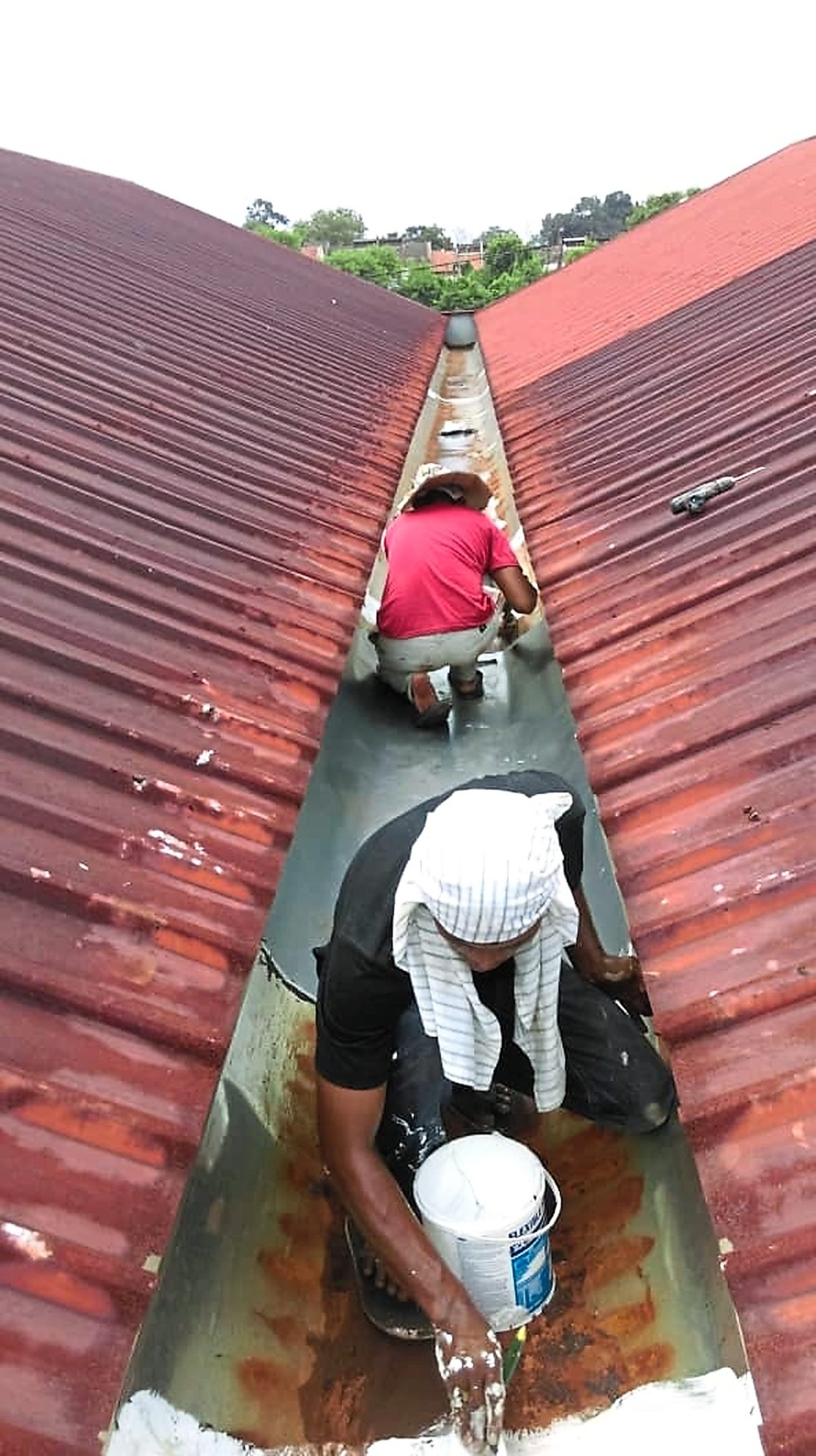 Workers repairing the broken gutters, which previously resulted in water leaking onto stalls during downpours.