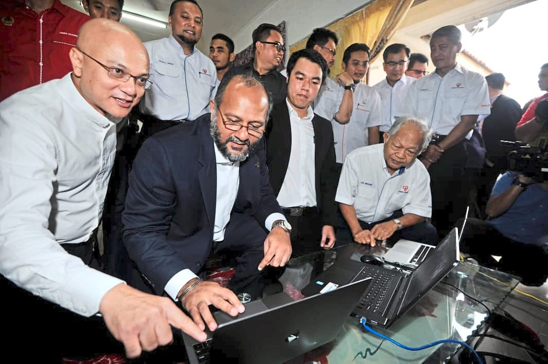 MCMC chairman Al-Ishsal Ishak (left) and Gobind (second from left) try out the high-speed broadband service after the pilot project of the NFCP in Jasin, Melaka.