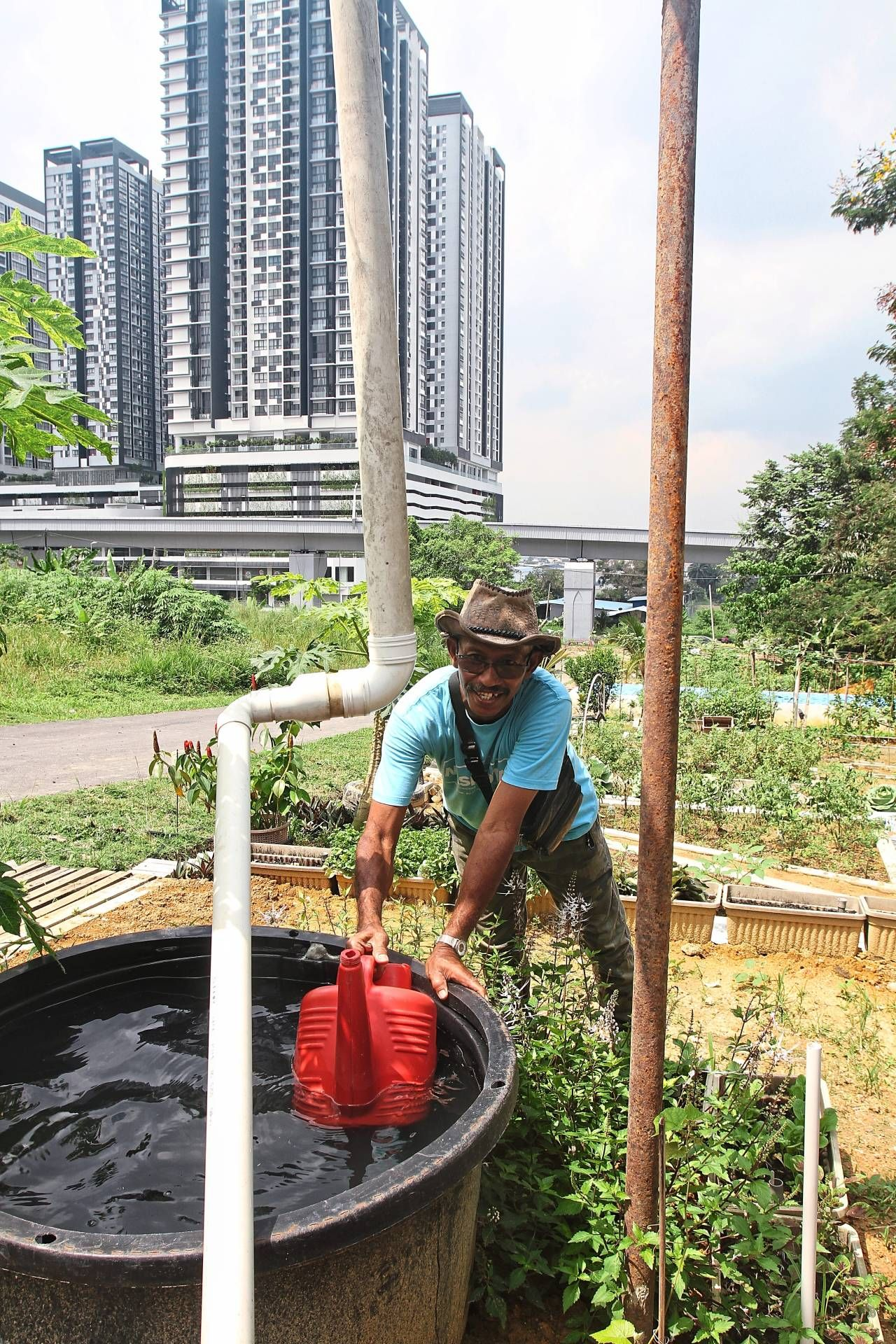 Villager Abdul Rani Selamat getting water for the plants in Kampung Selamat's urban farm.