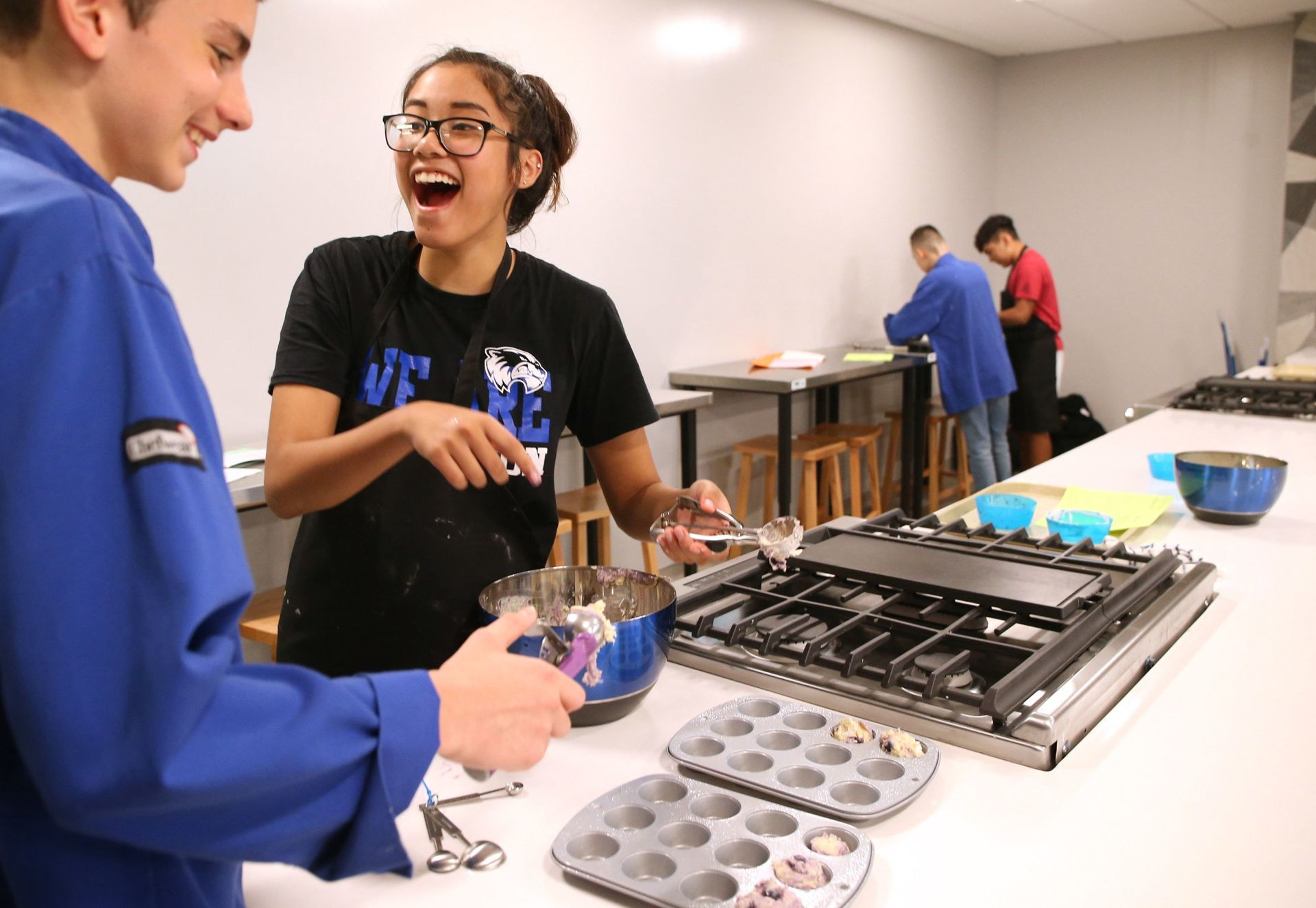 Freshmen students preparing blueberry muffins in the new culinary lab.