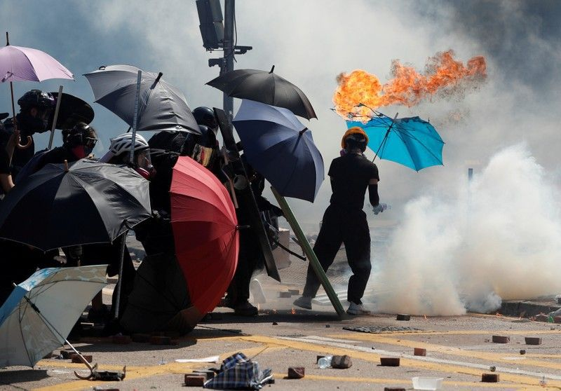 A protester's umbrella catches on fire during clashes with police outside Hong Kong Polytechnic University (PolyU) in Hong Kong, China November 17, 2019.    REUTERS/Adnan Abidi
