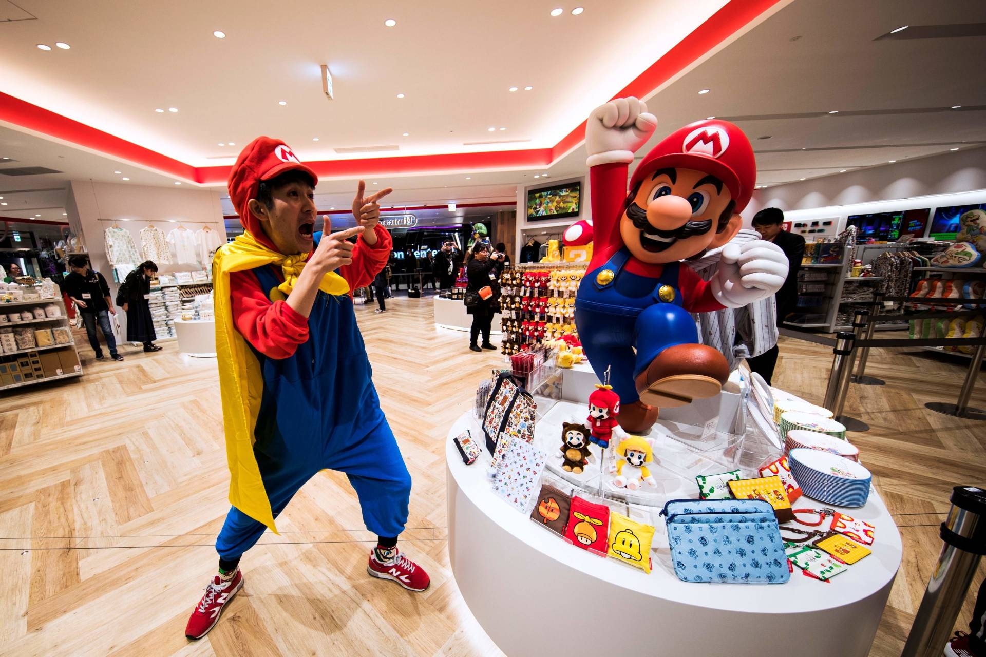 A man wearing a Mario costume next to merchandise at a new Nintendo store in Tokyo. — AFP