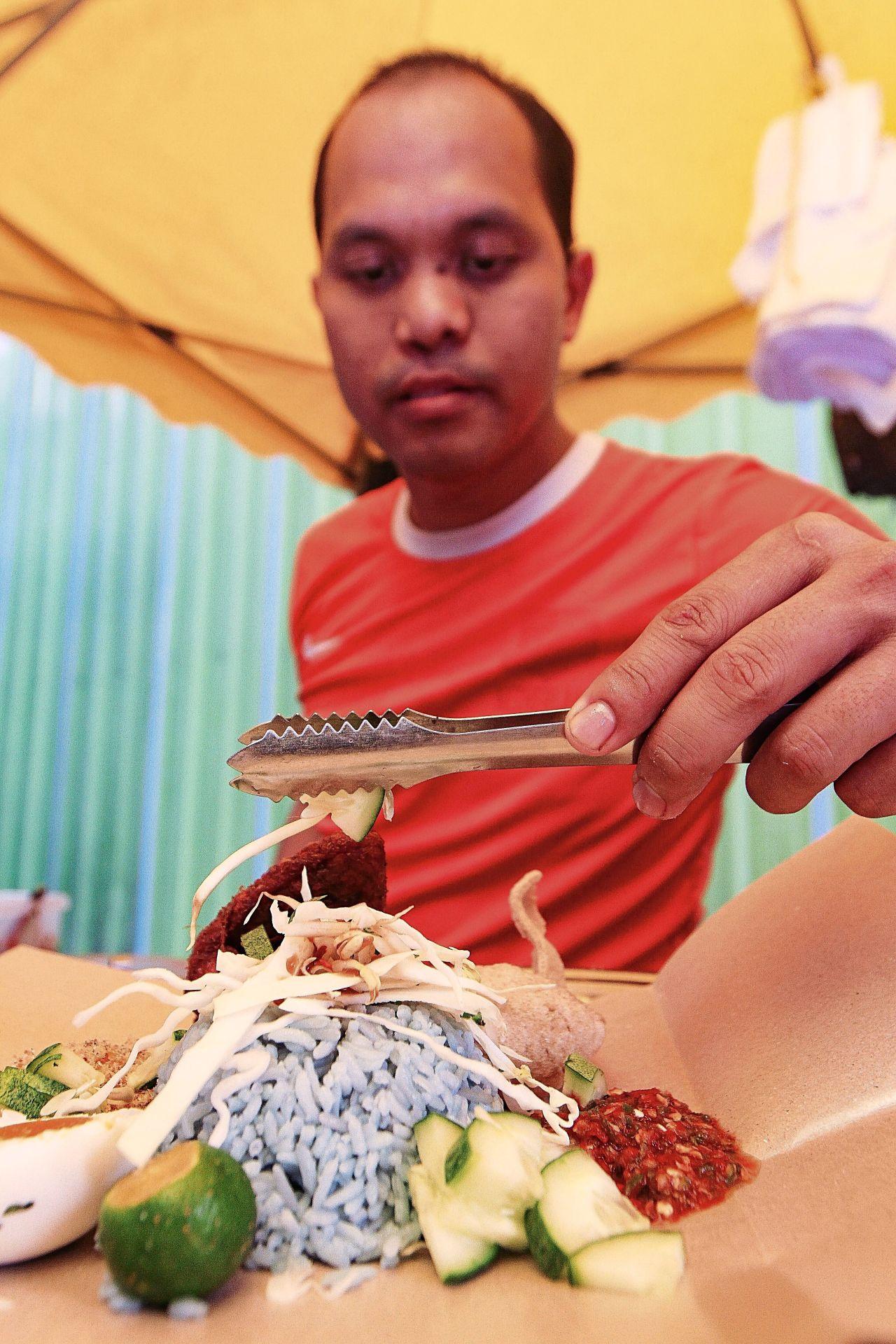 Suhaib putting the last of the garnishing on the nasi kerabu at the stall behind Menara KH in Jalan Sultan Ismail, Kuala Lumpur.