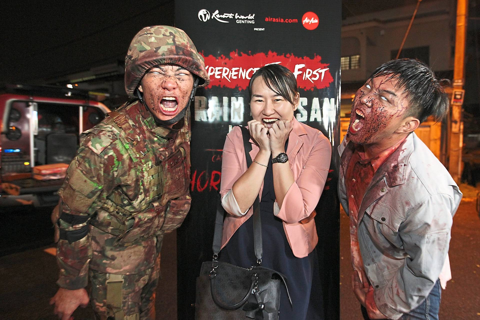 Tan, who  won a Train  to Busan Horror House ticket, with the zombies  at Chow Yang night market.