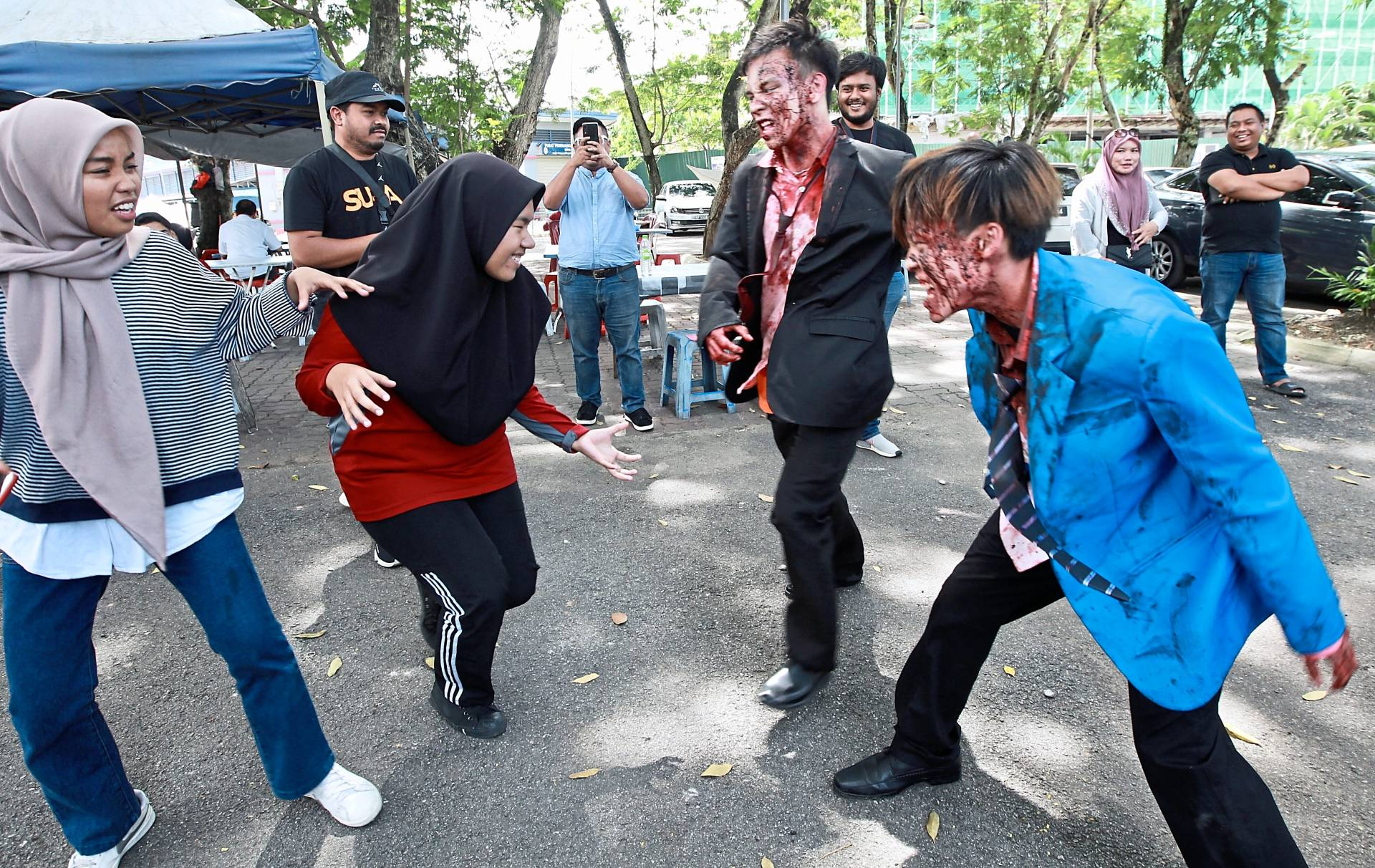 Visitors cringing at the sight of the zombies near Tasik Taman Sri Rampai, Kuala Lumpur.