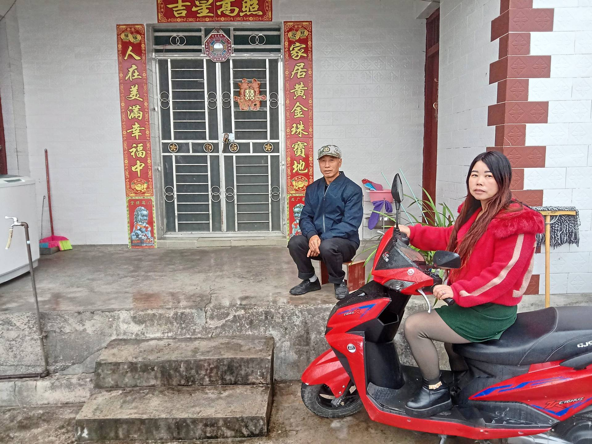 Chen Jia Jie (right) on her motorbike in front of her new house built with the help of government subsidy in the village of Wangou in Jinchang, Yunnan.