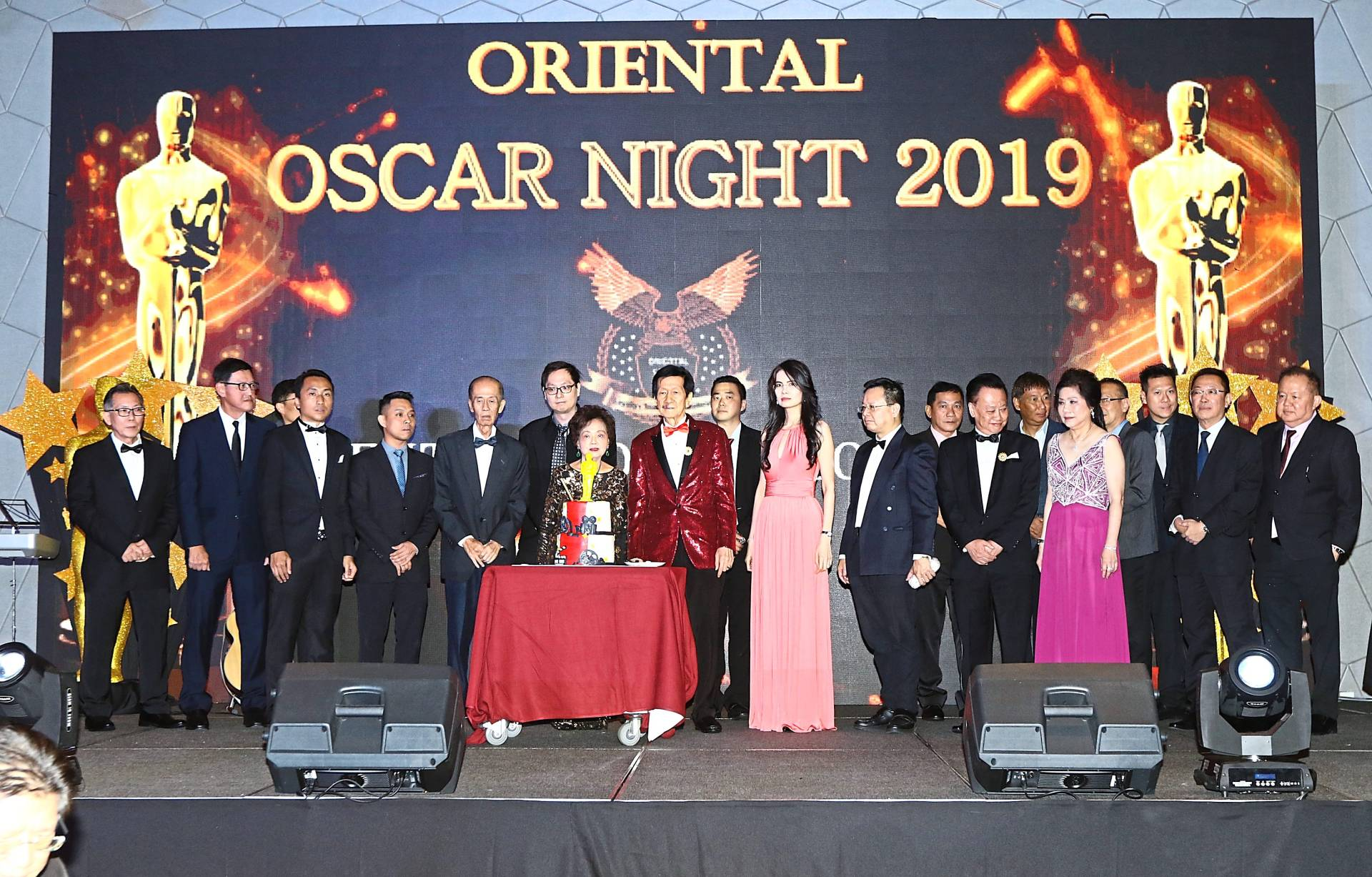 Wong (in red suit), his wife Loh Ean (at Wong's right), daughter Susan Wong (in pink) and son Tony Wong (behind Loh Ean) are joined by management staff during a cake-cutting ceremony at the Oriental Sports Club Oscar Night 2019 Annual Dinner.