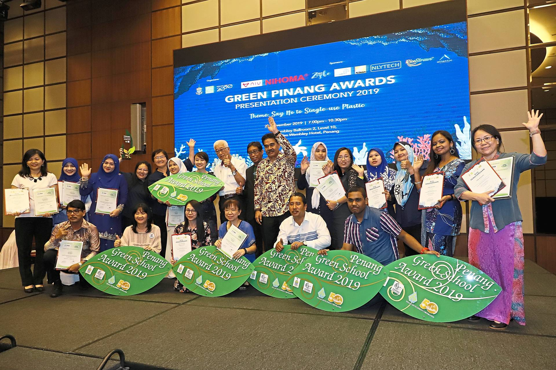 Penang Water Supply Corporation chief executive officer Datuk Jaseni Maidinsa (in batik) and state welfare and caring society committee chairman Phee Boon Poh (white shirt, second row) posing with recipients of the Penang Green School Award 2019.