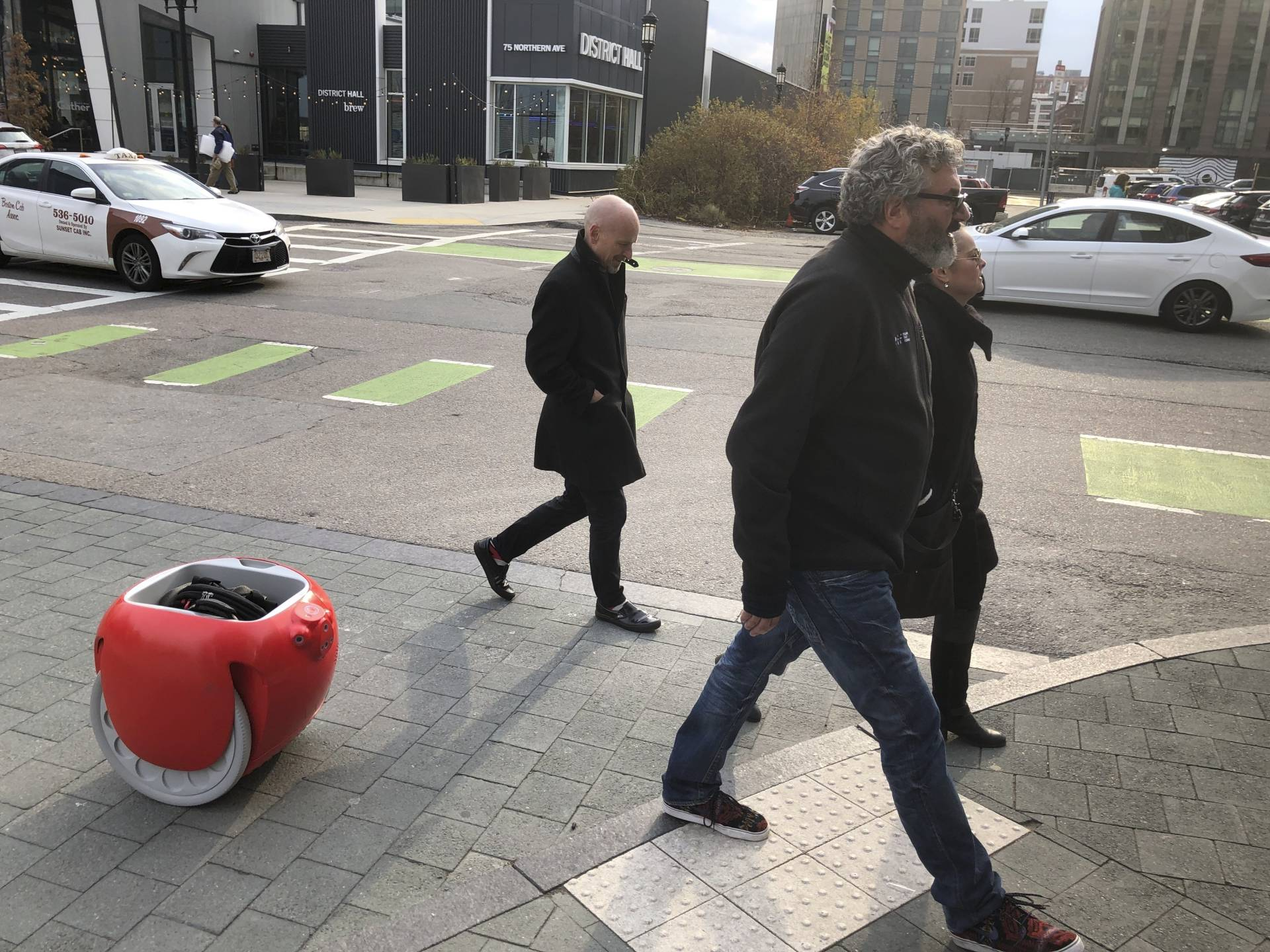 Lynn, center, is followed by his company's Gita carrier robot as he crosses a street in Boston. The two-wheeled machine is carrying a backpack and uses cameras and sensors to track its owner.