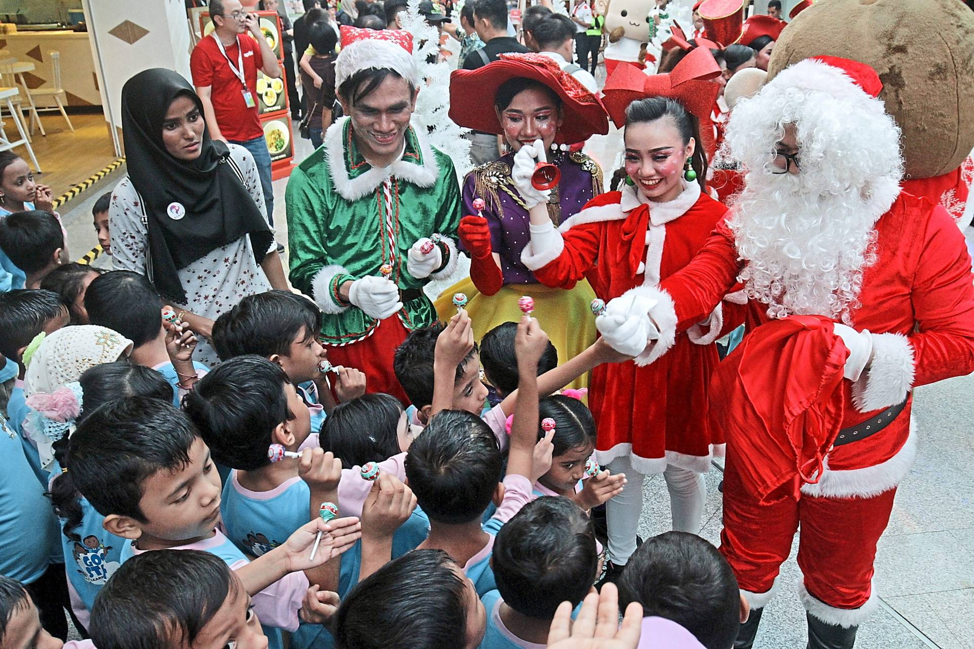 Santa Claus and Santarina distributing lollipops to the kids.
