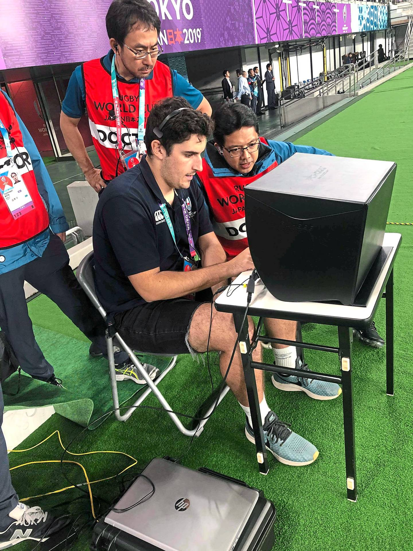 Dr Azril (right) reviewing head impact clips on video replay with his medical team members during halftime of the quarterfinals between Japan and South Africa.