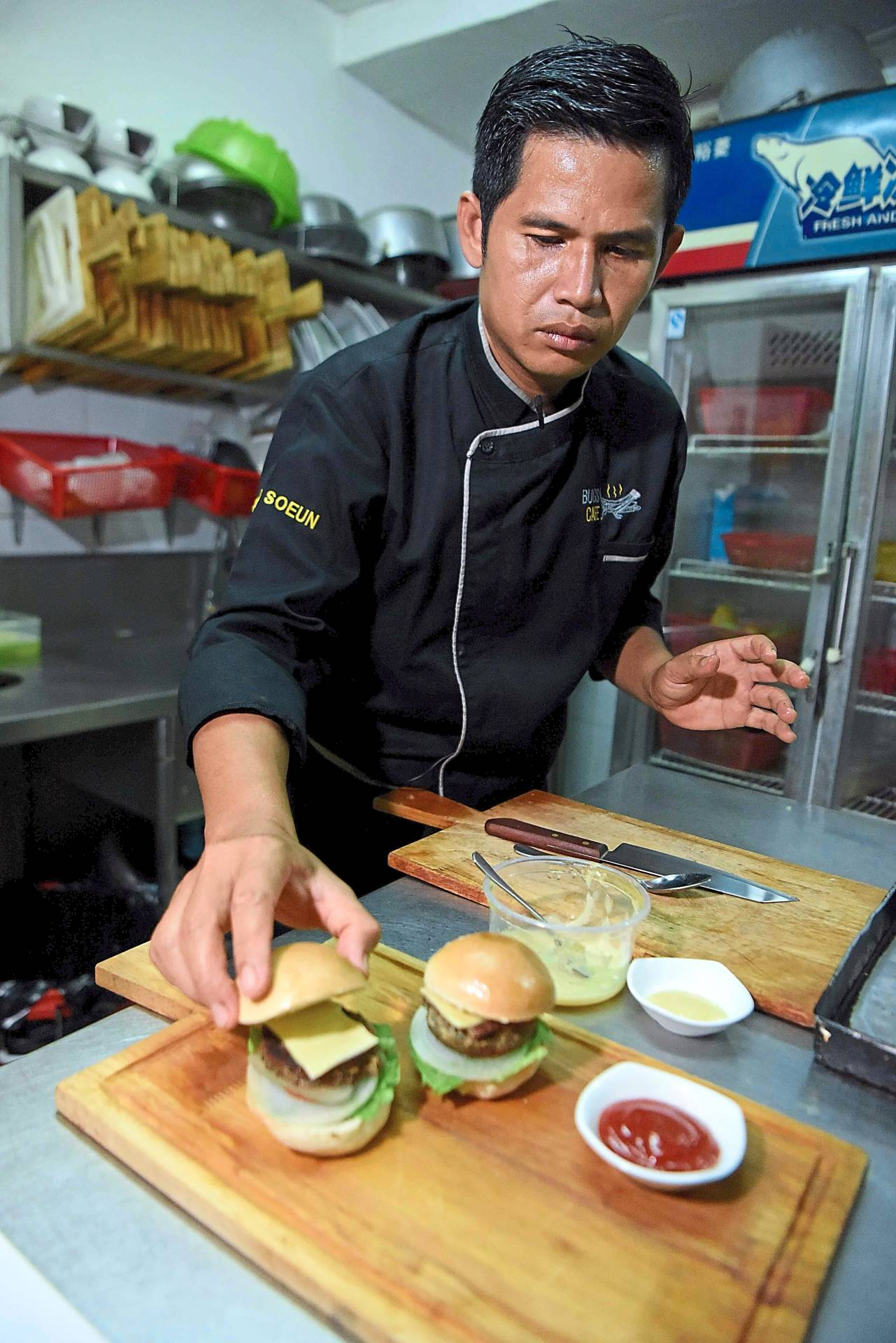 Acquired taste: Soeun preparing a 'bug mac' with a patty of pureed ant, bee, silkworm and cricket topped with a slice of cheese and pickle at Bugs Cafe in Siem Reap province.