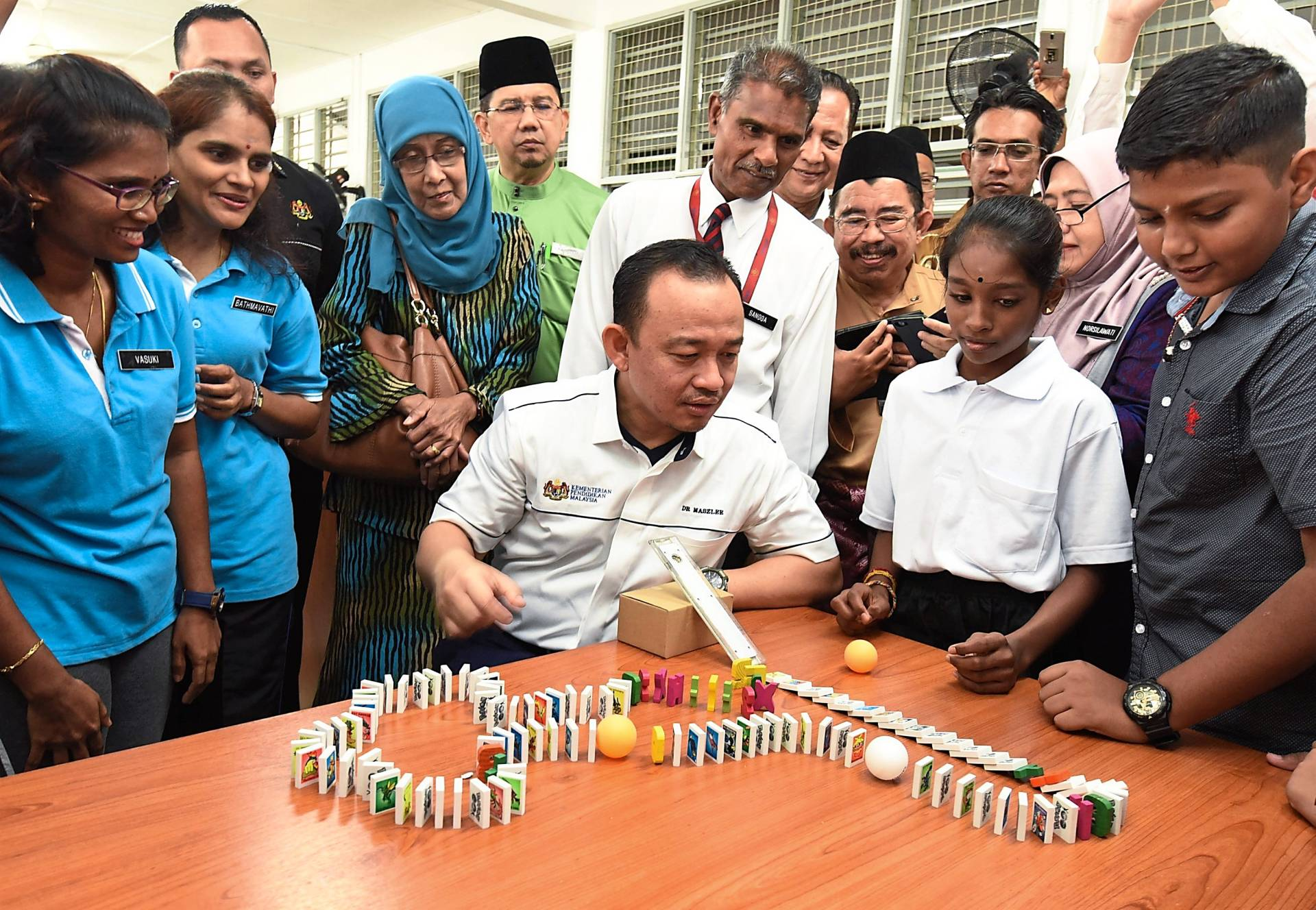 Maszlee (seated, centre) observing the demonstration on dominoes during a visit to SJK (T) Sungai Ara in Bayan Lepas, Penang.